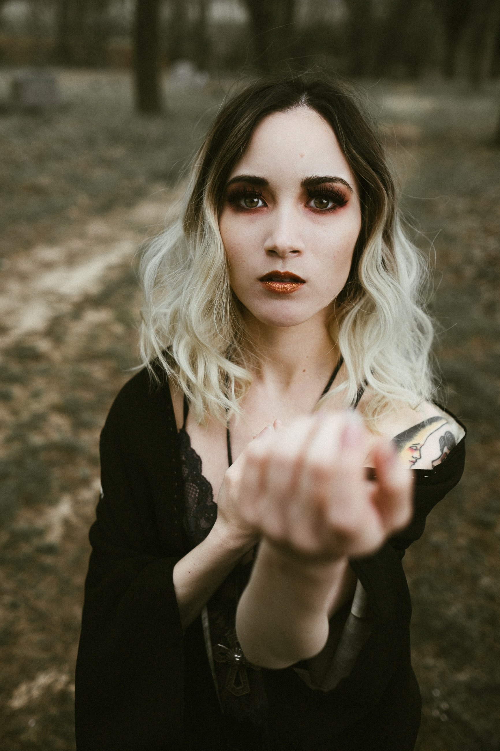 Blonde woman with a tattoo on her arm wearing black in the woods.