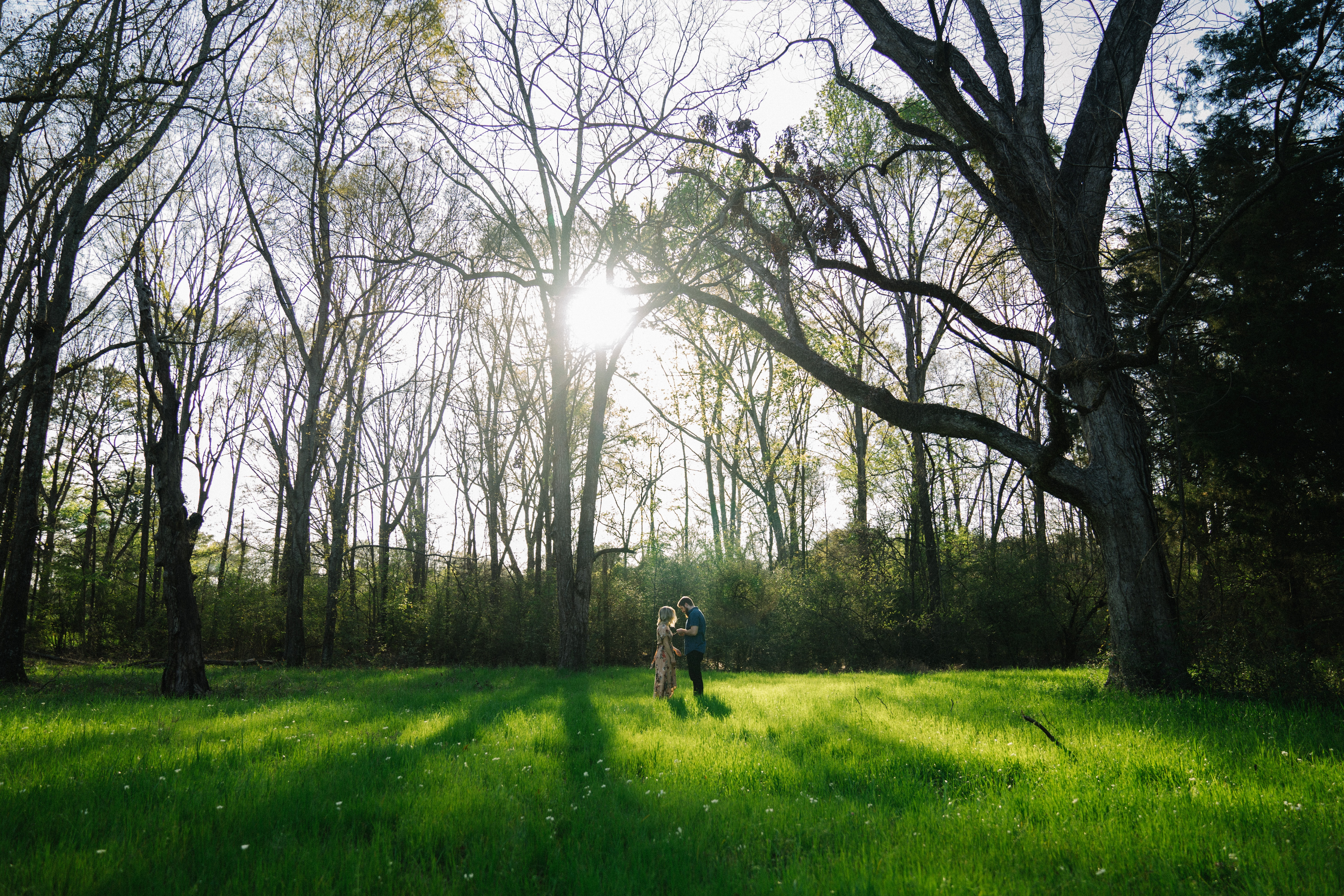 A couple stands on the grass among trees, leaning against one another