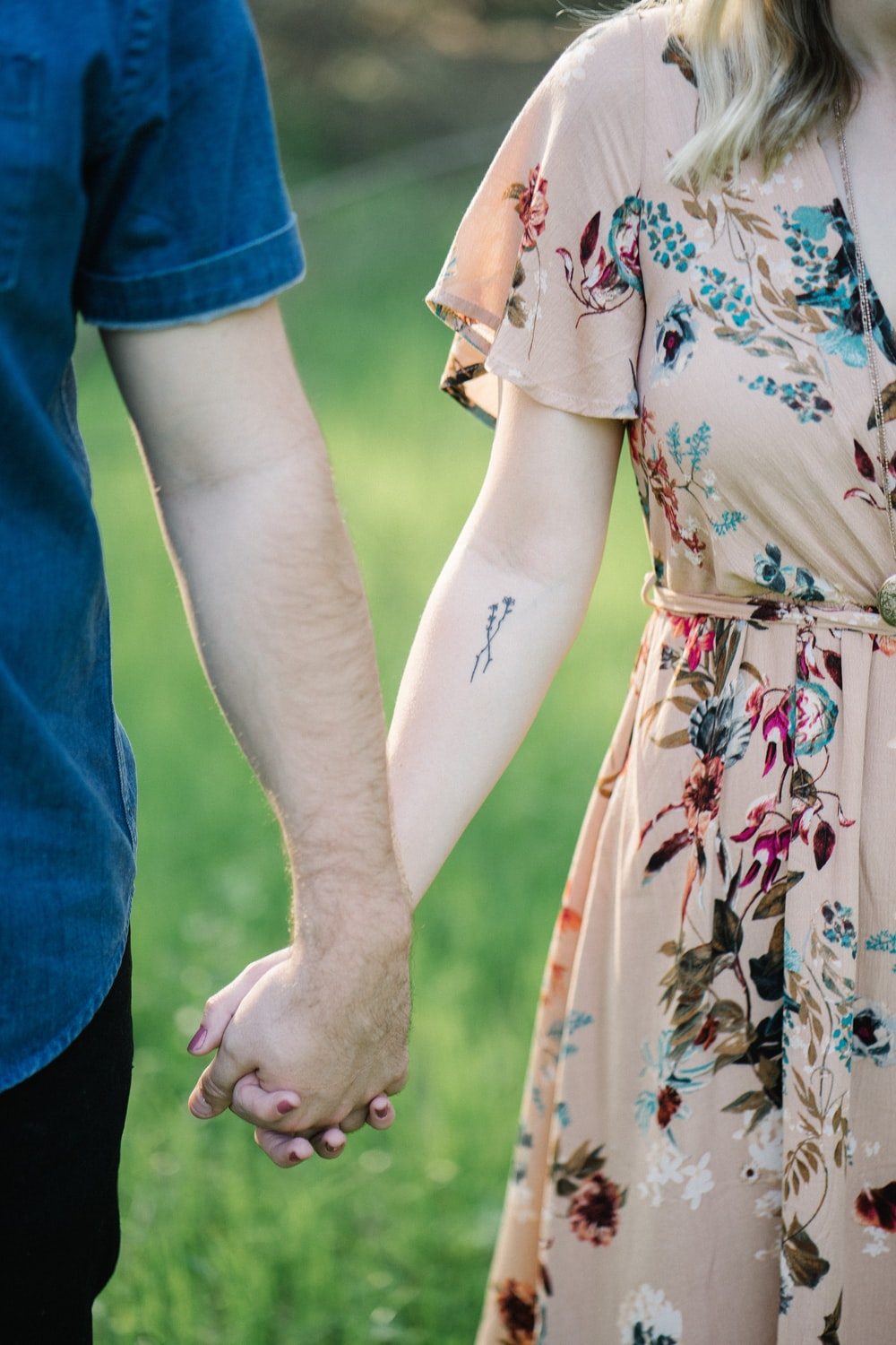 selective focus photography of man and woman holding there hands