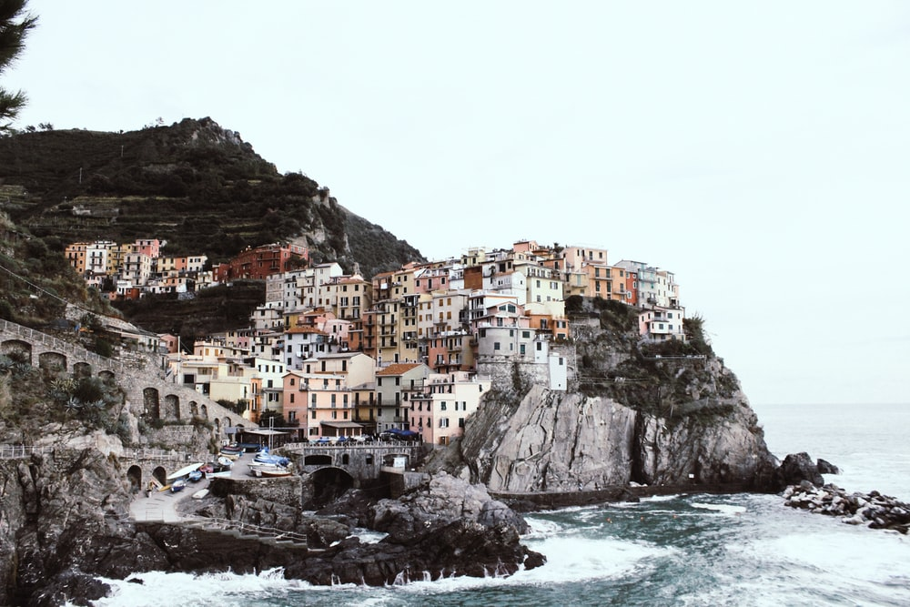 white and brown houses on cliff beside a sea at daytime