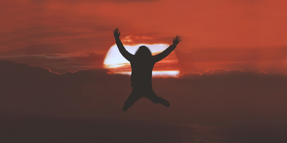 silhouette of person doing jumpshot during sunset