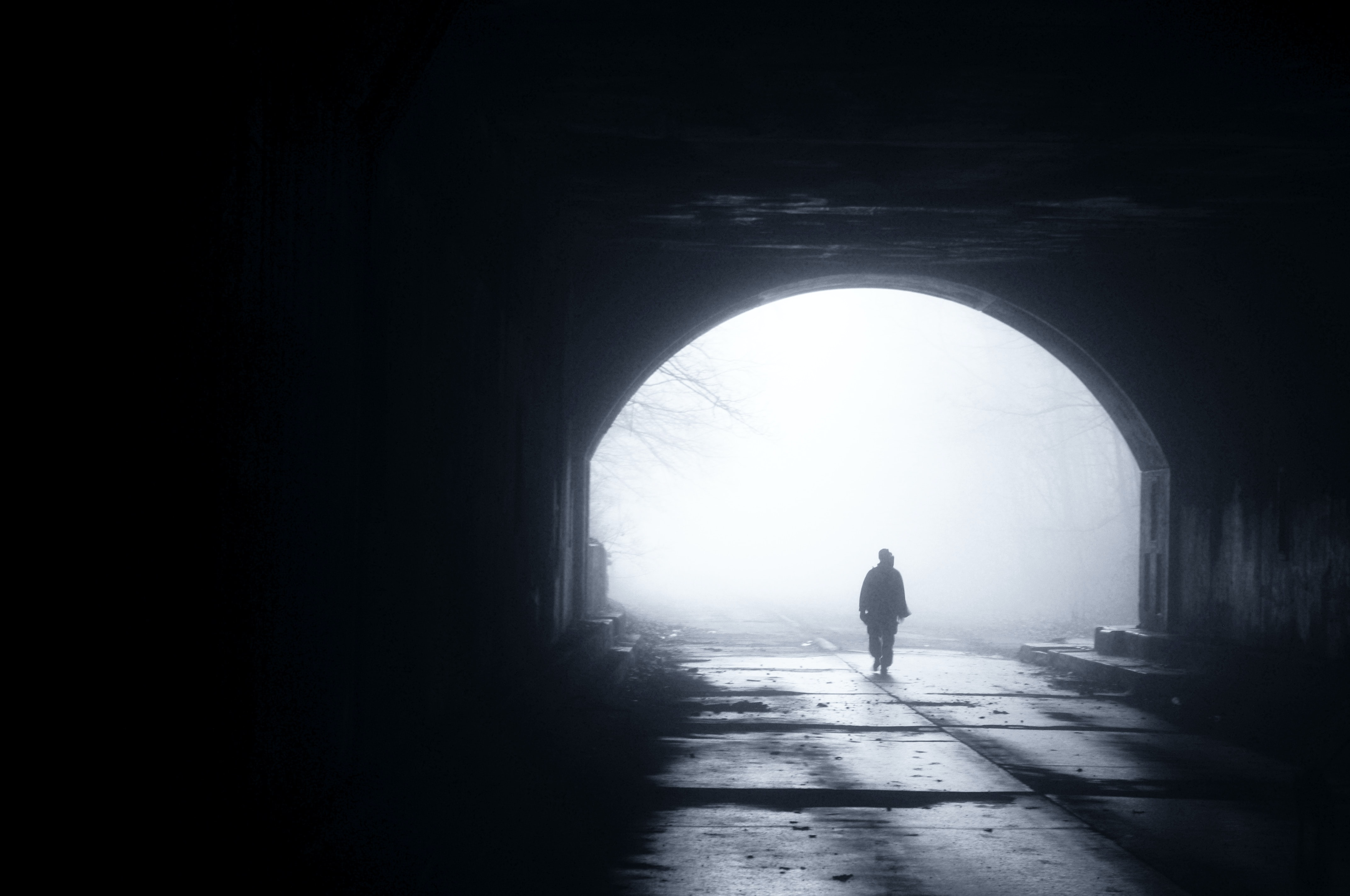 silhouette of person walking out from tunnel during daytime