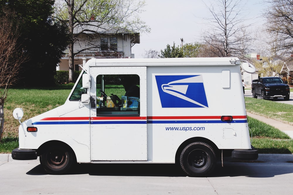 A mailman sitting in a mail truck sorting mail parked outside of a house in Tulsa