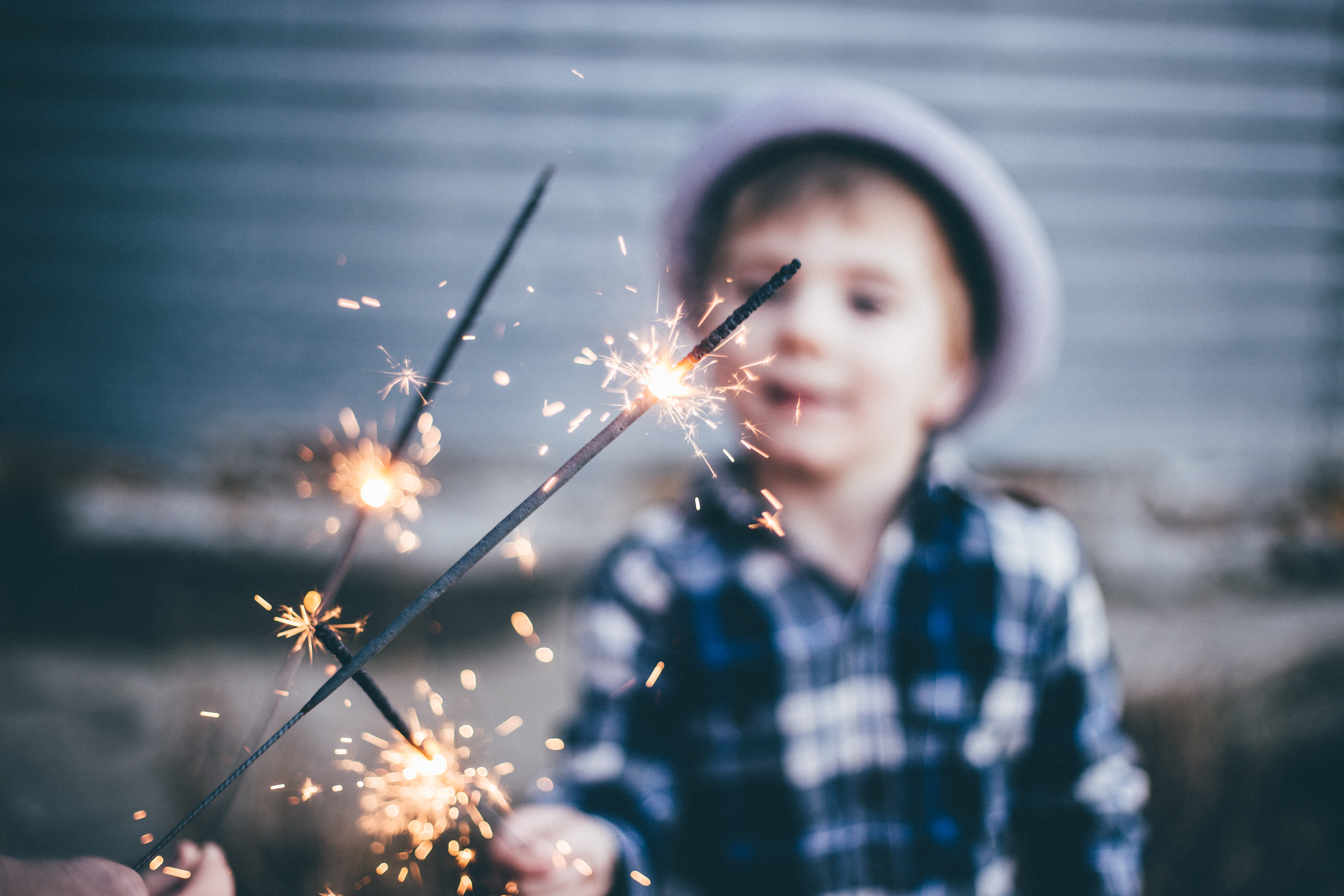 closeup photo of boy wearing blue and white plaid sport shirt holding firework