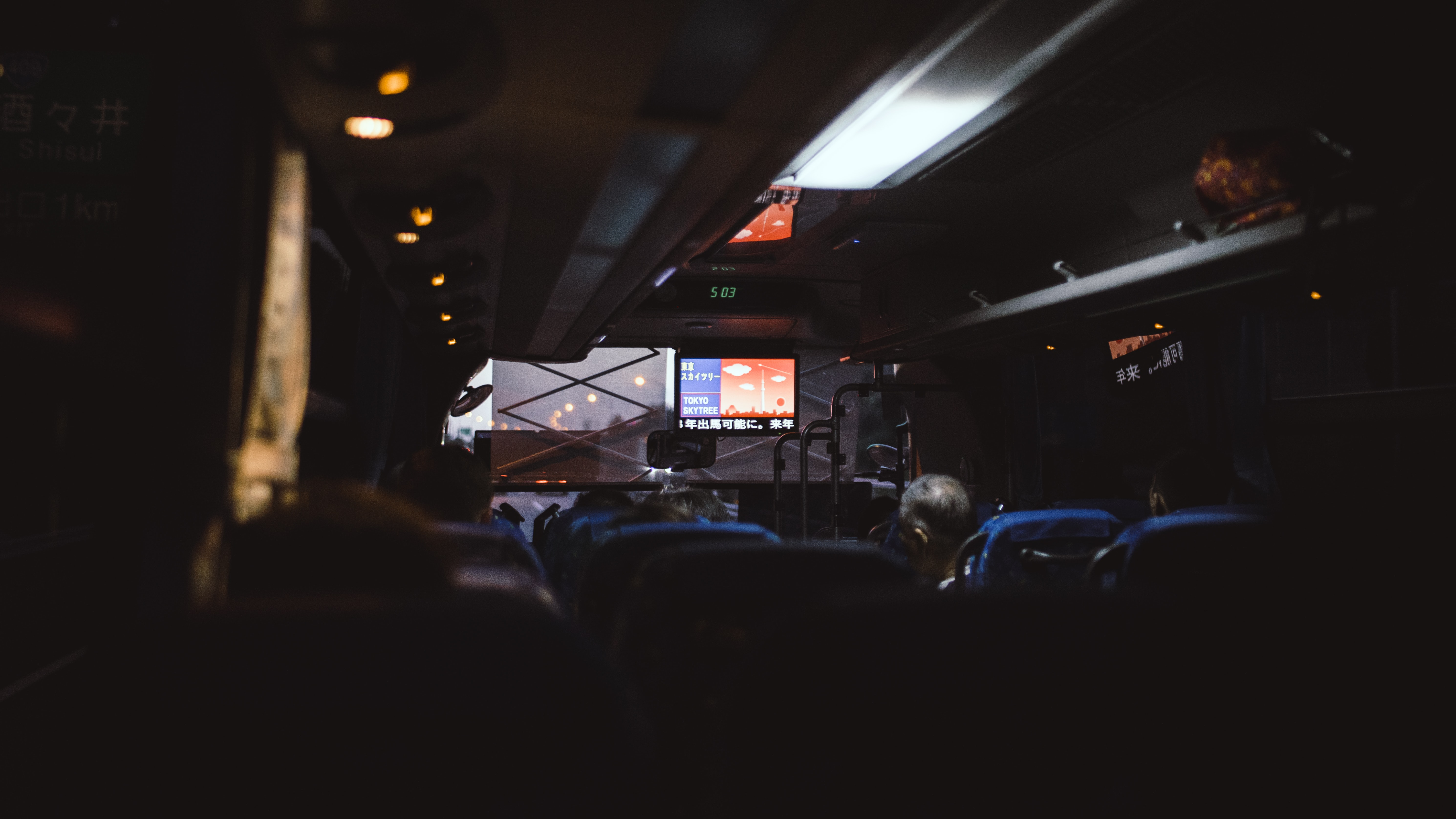 The dim interior of a coach driving through Tokyo