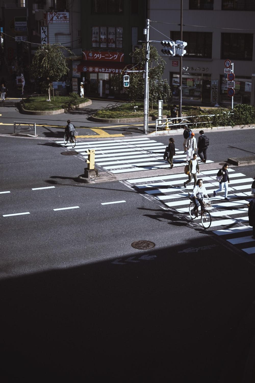 people walking on pedestrian lane across road during daytime