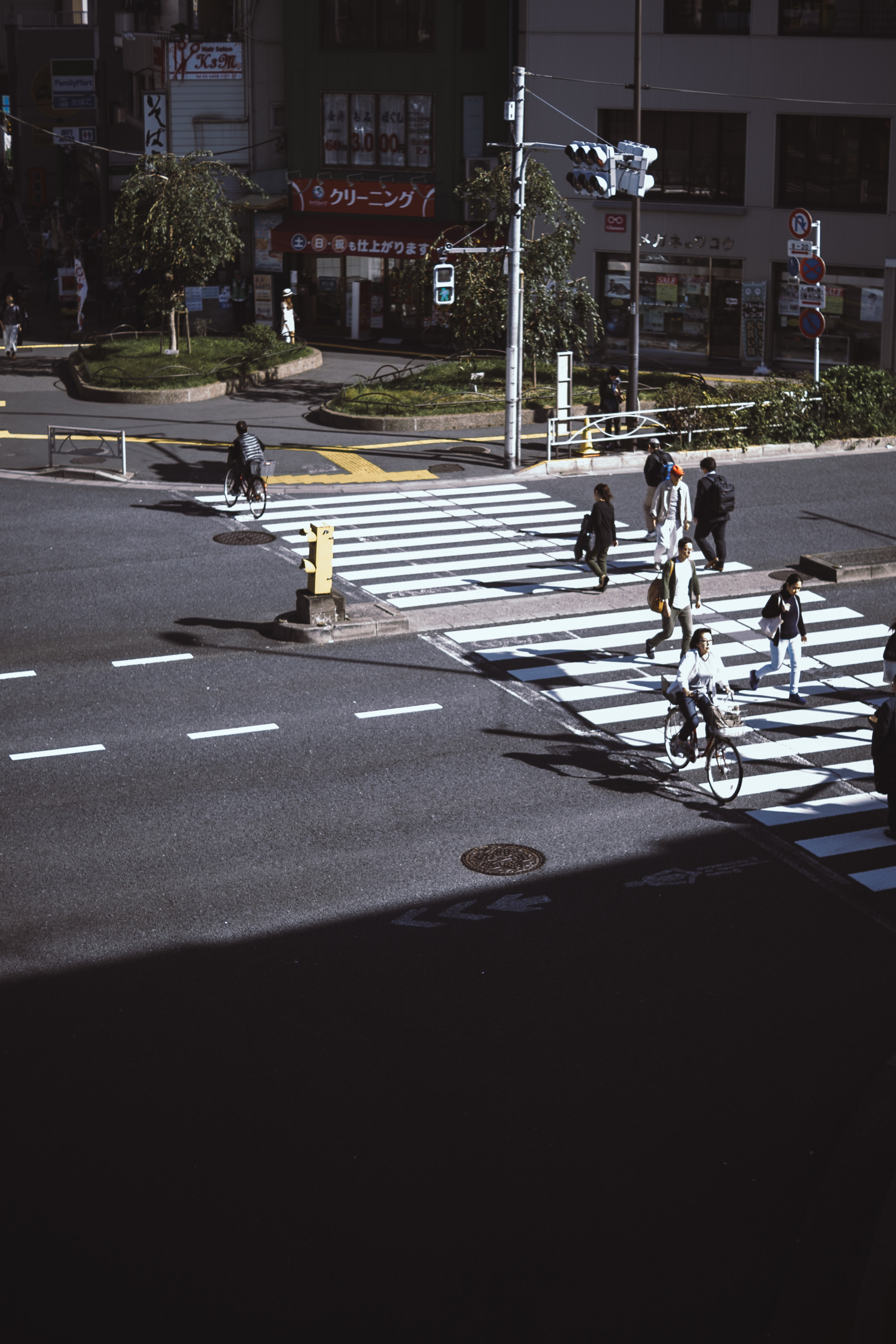 People walking and riding bicycles through a pedestrian crosswalk in Taito