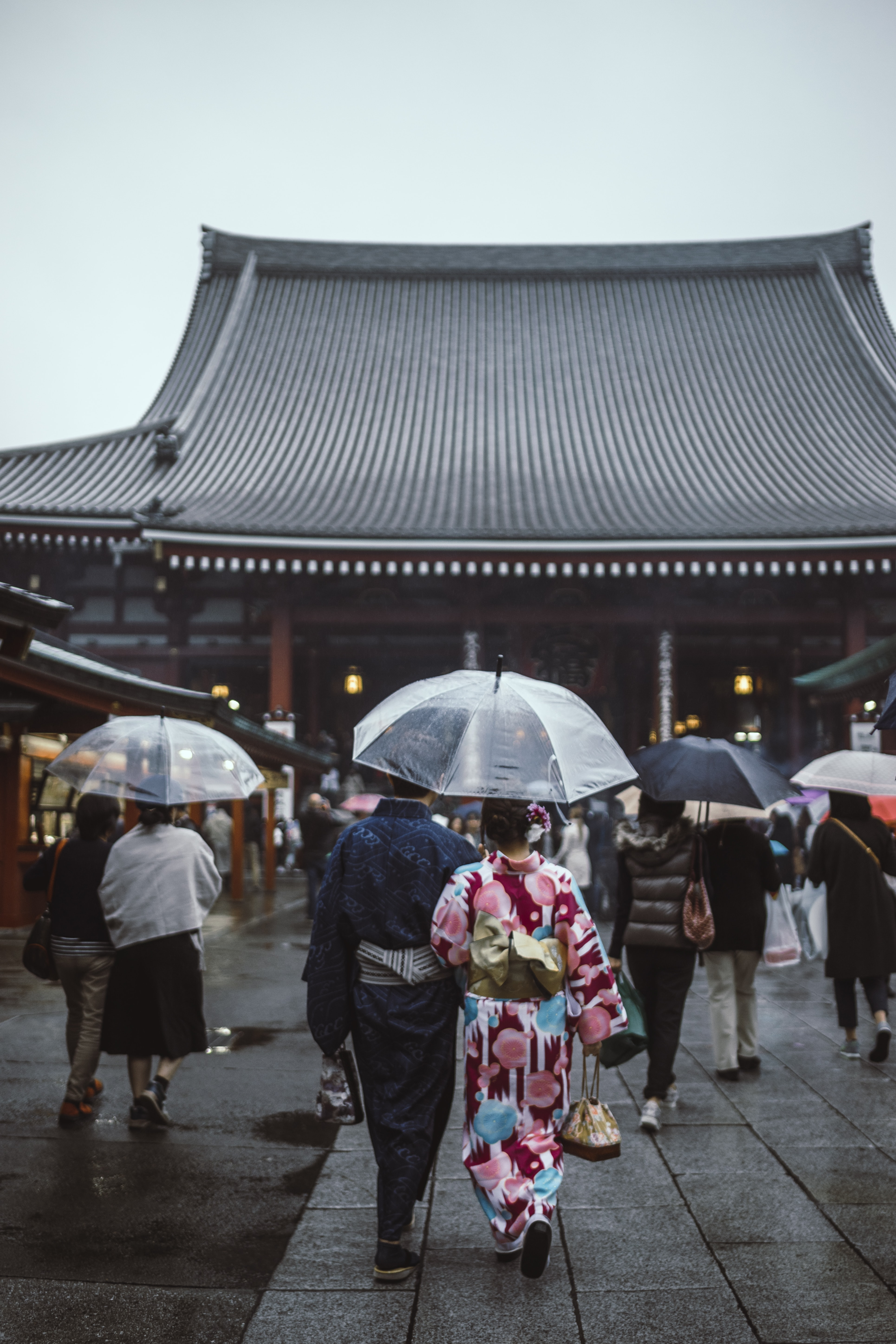 people walking on street while holding umbrellas going to pagoda