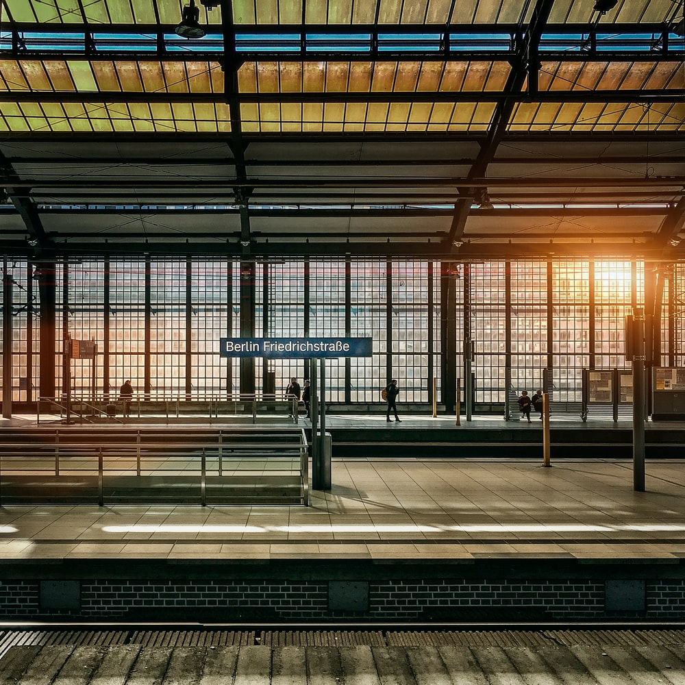 people standing inside station during golden hour