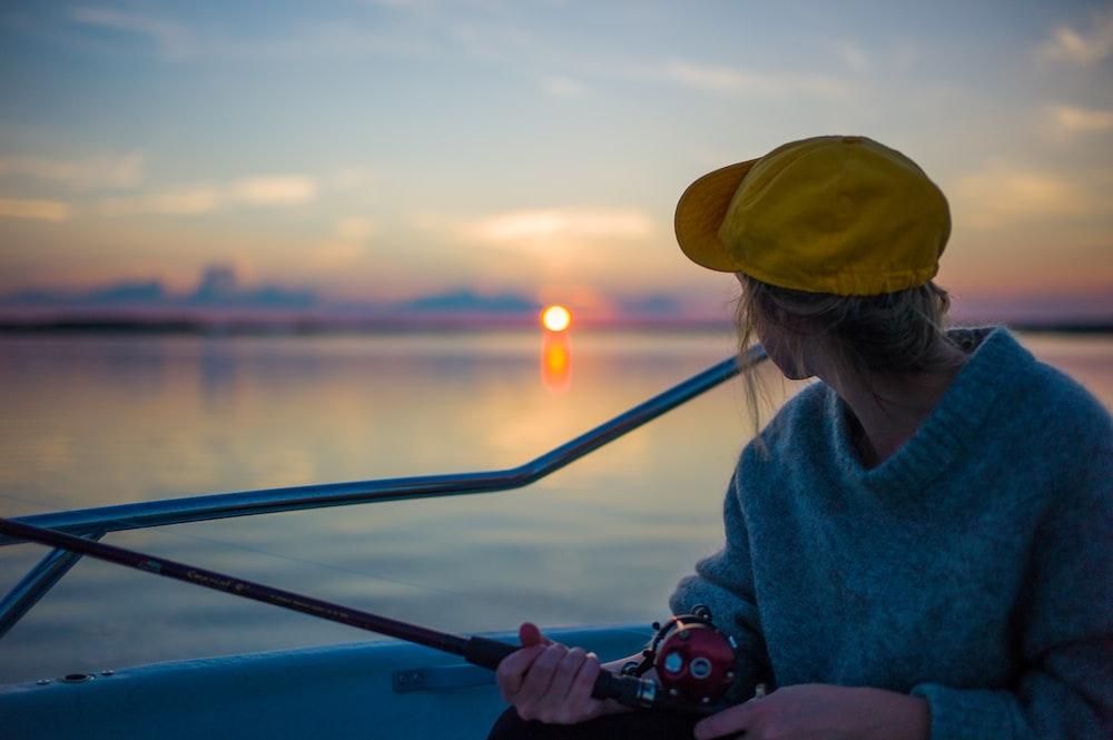 man holding black fishing rod while facing body of water
