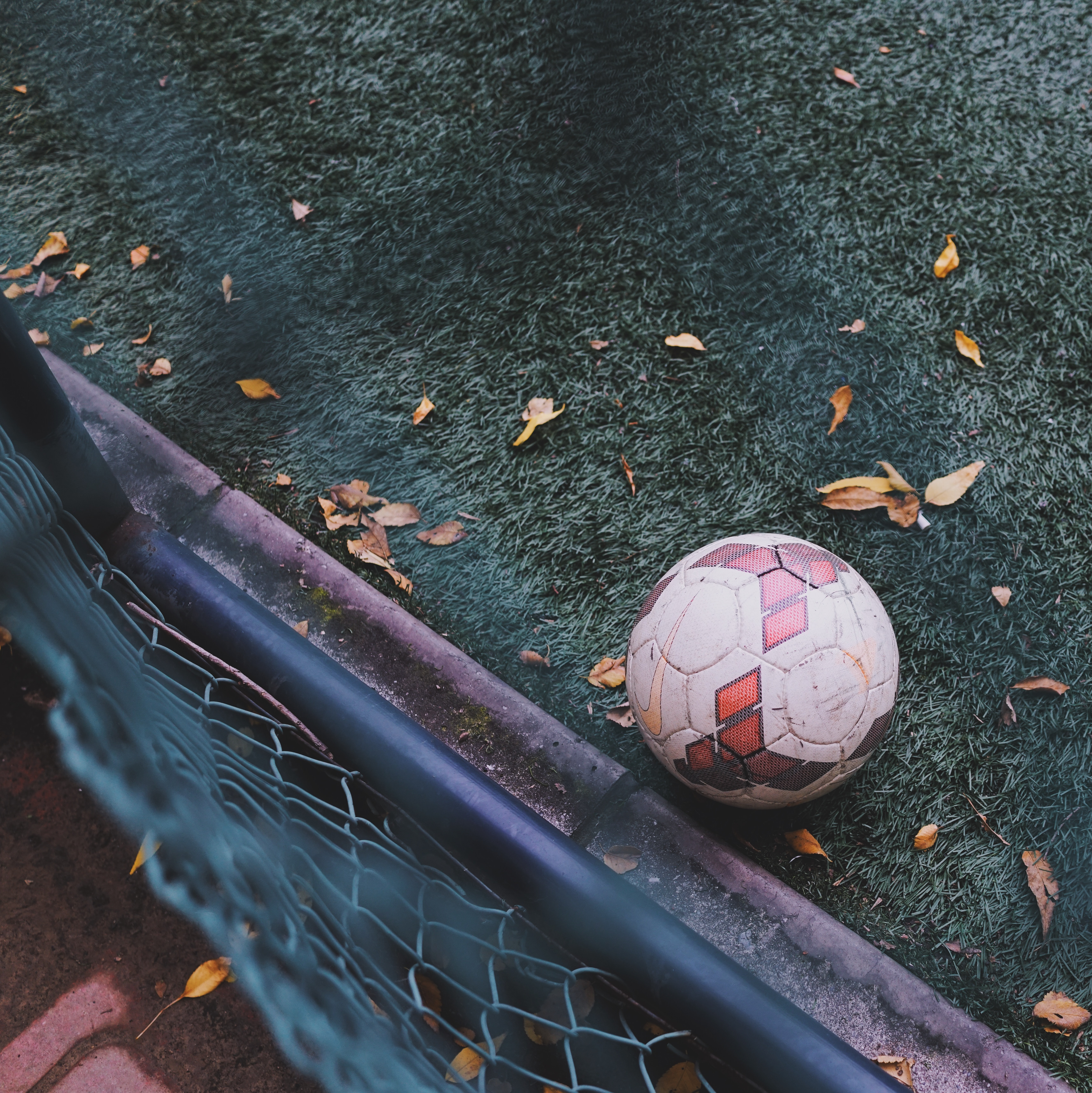 View over the fence on the soccer ball sitting on a green turf pitch