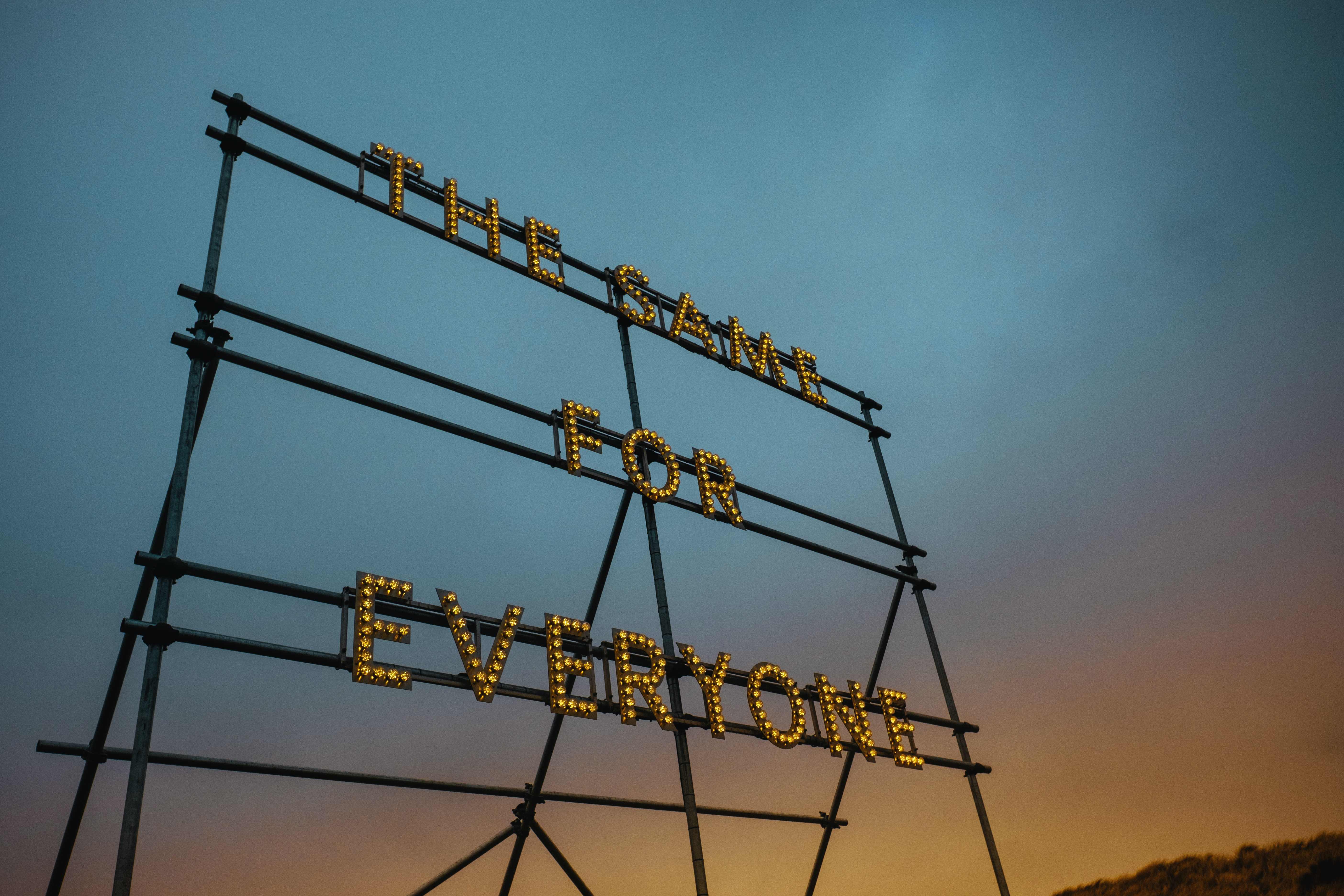 low angle photography of the same for everyone LED signage on tower under gray sky