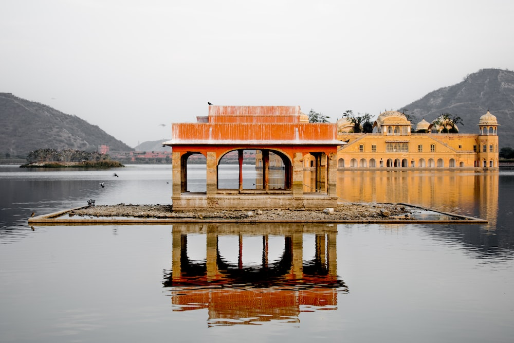 brown concrete building surrounded by water during daytime
