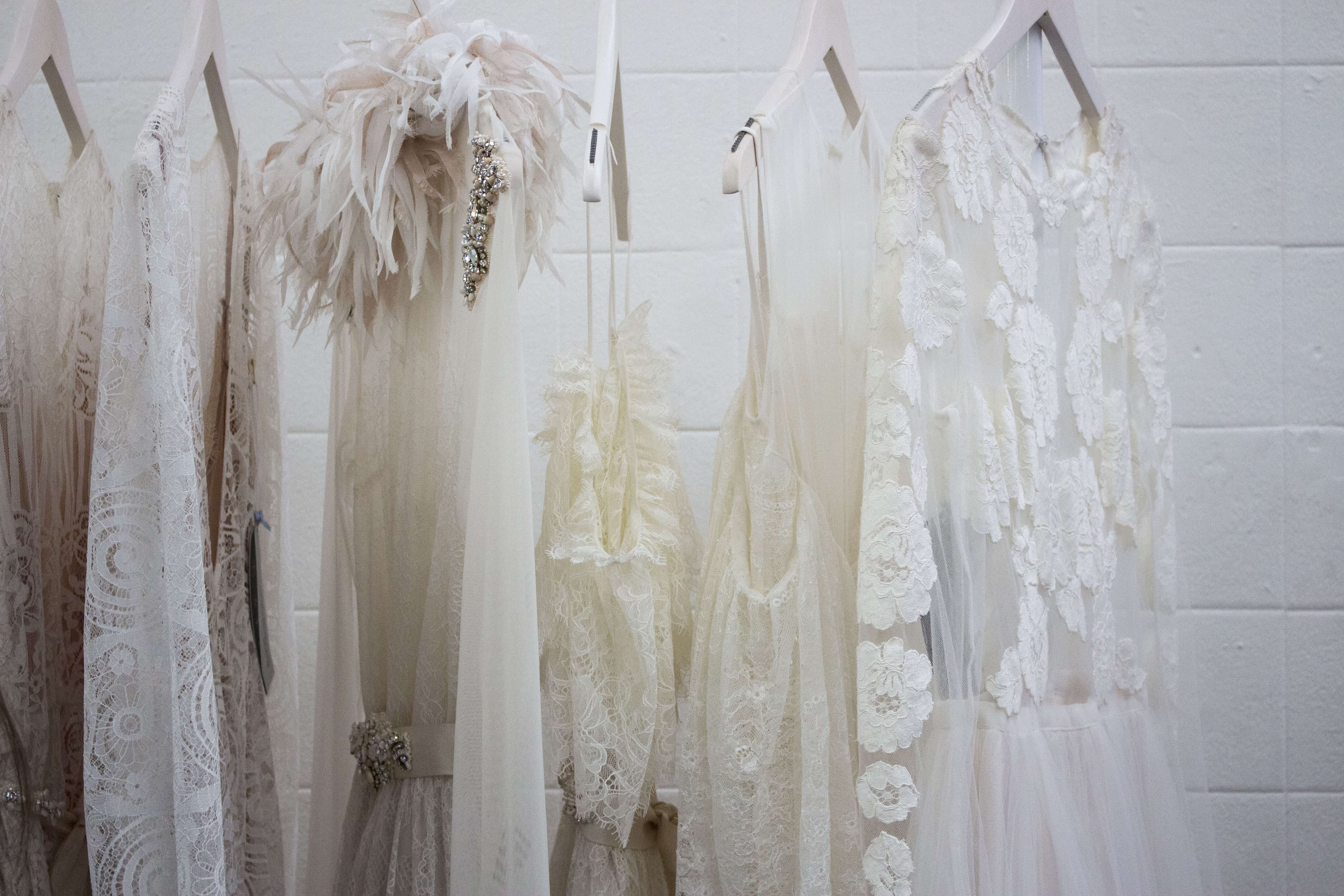 Thin wedding dresses hang in front of a white brick wall at Old Truman Brewery
