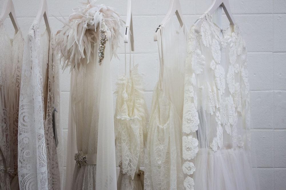 six women's white dresses hanging on hangers