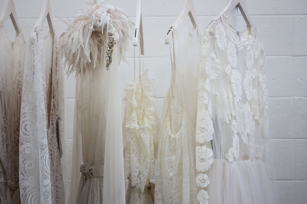 six women's white dresses hanging on hangers