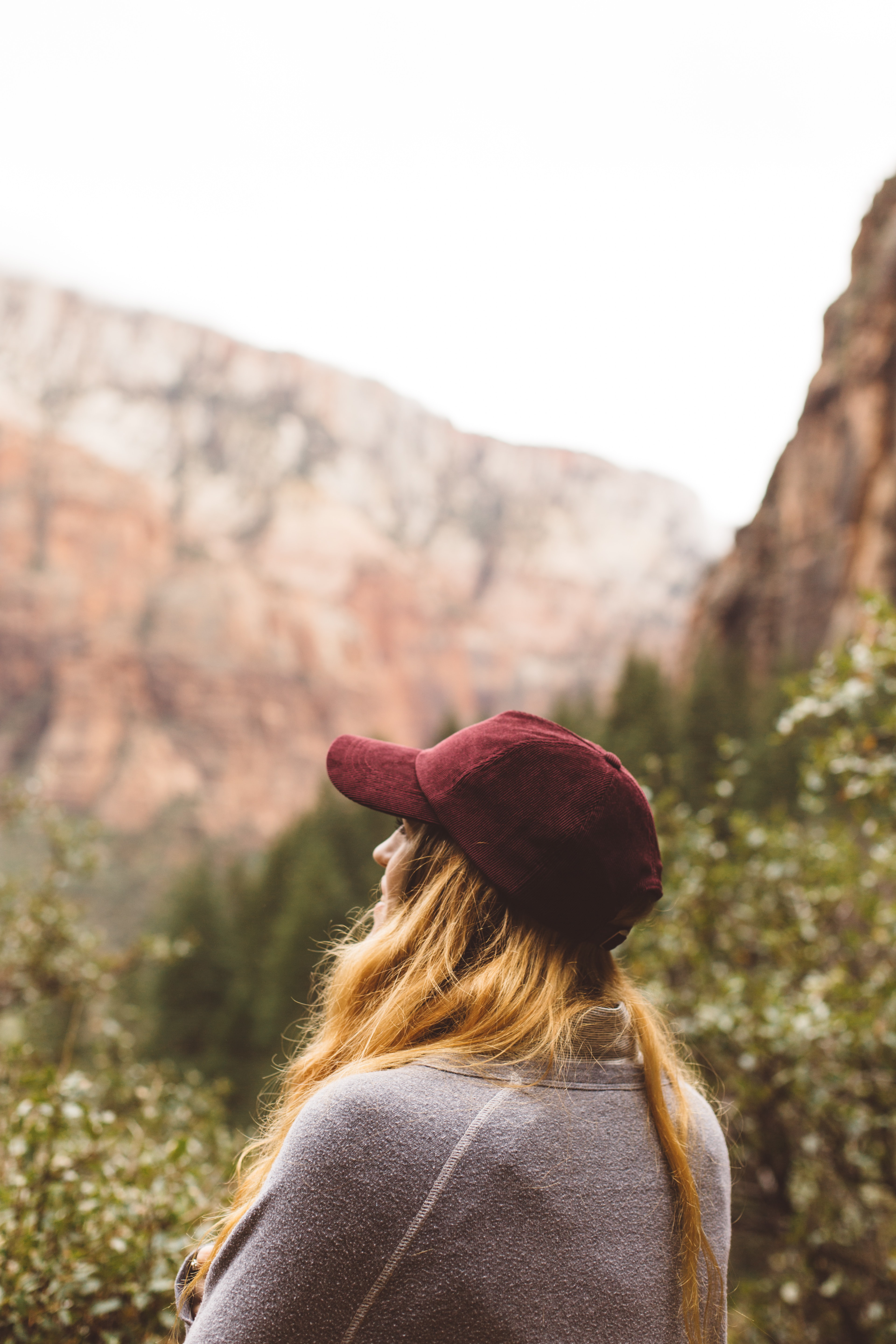 selective focus of woman in gray sweater standing far mountain
