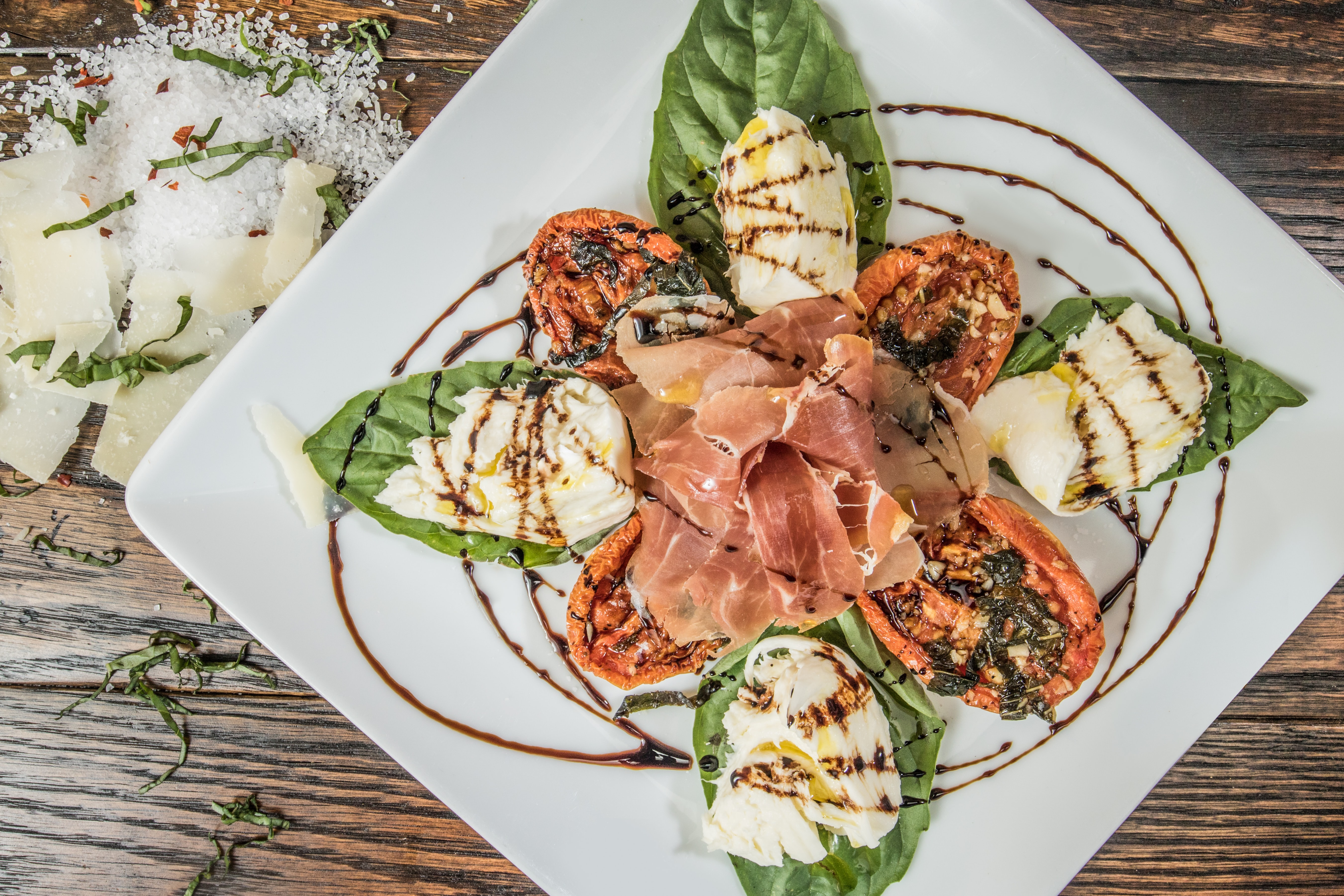 Italian salad with basil leaves, pancetta, grilled tomatoes, and cheese