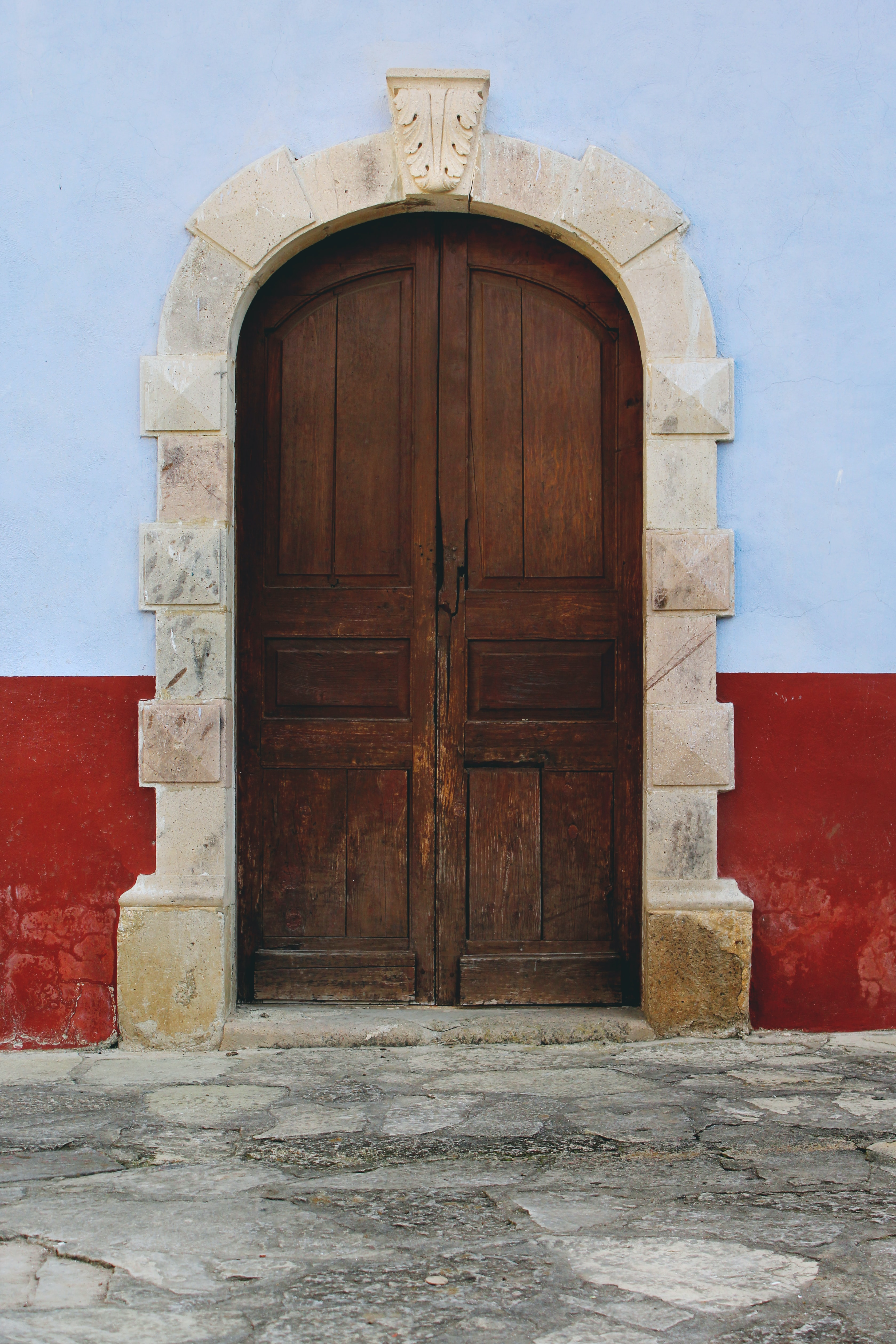 Large domed wooden door with white stones on the border and a red and blue wall flanking it on a stone street