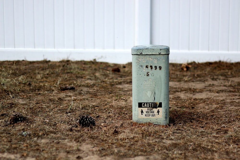 gray trash bin on brown grass