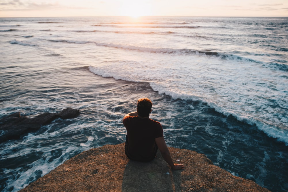 person sitting on cliff facing body of water