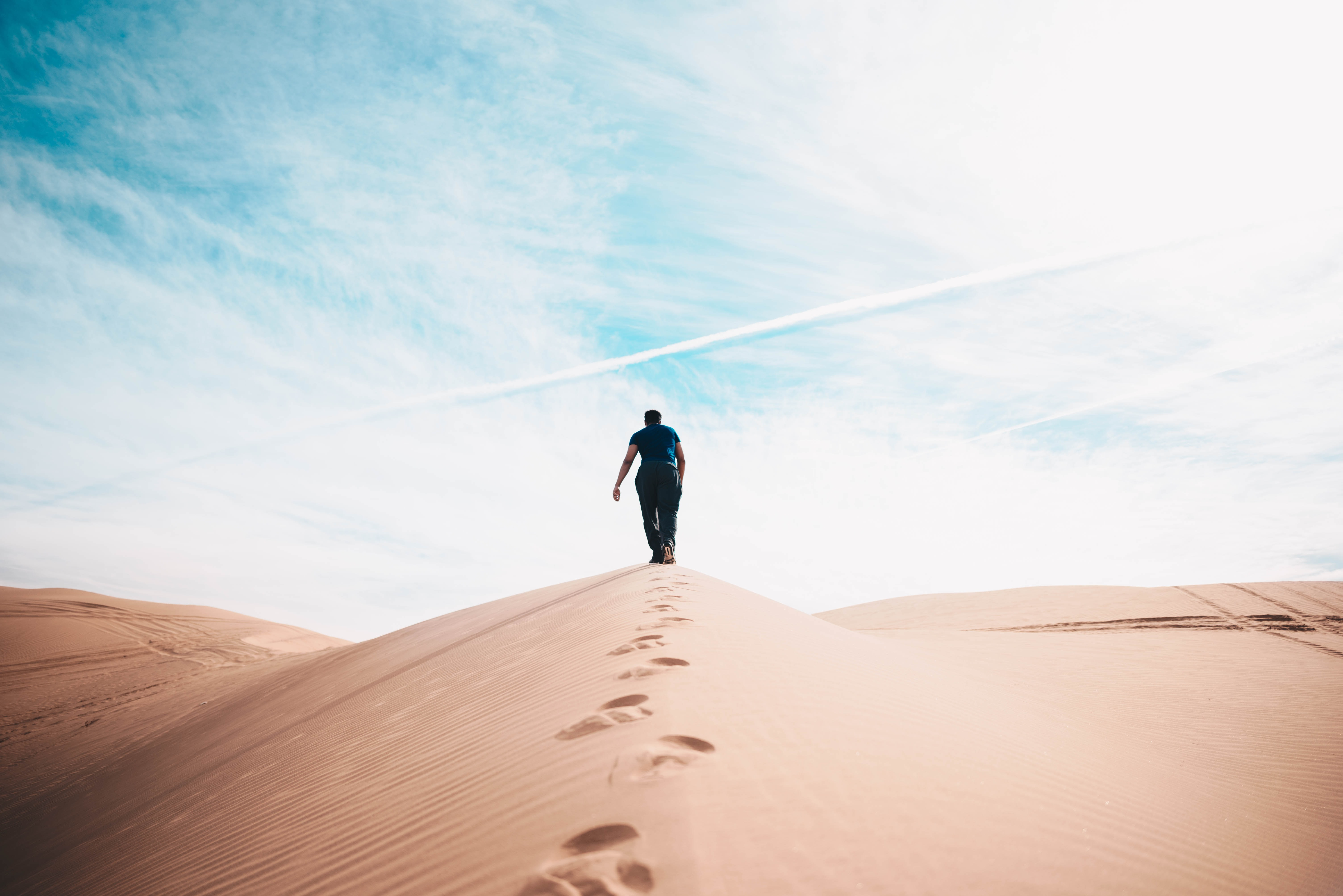 A person walking in the desert leaving footprints with cloud in the deserts Algodones Dunes