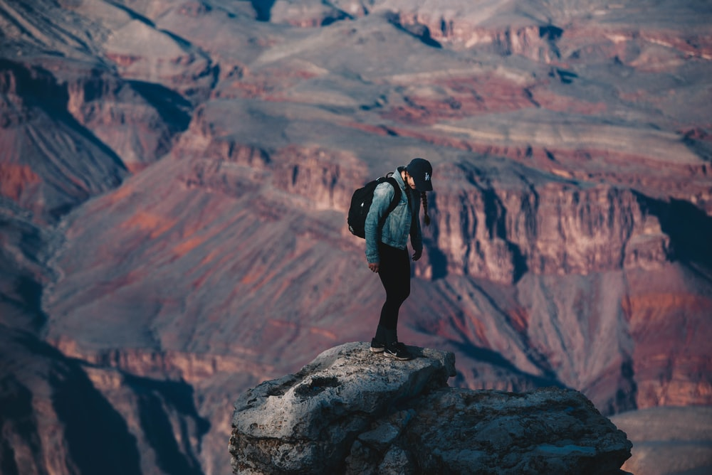 man standing on rock cliff overlooking canyon during daytime