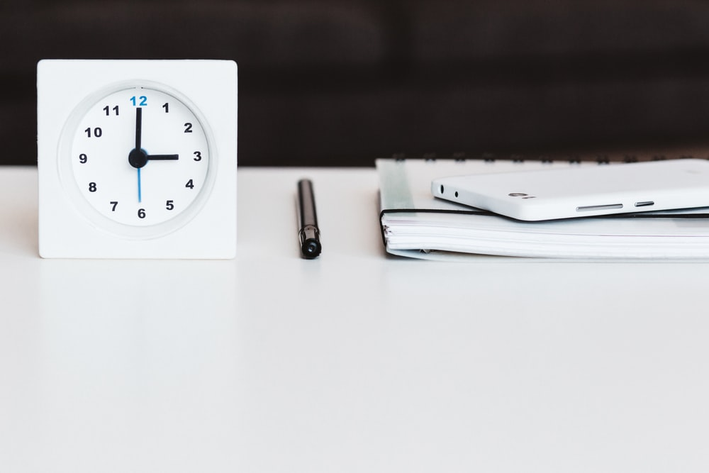 white desk clock near pen and book