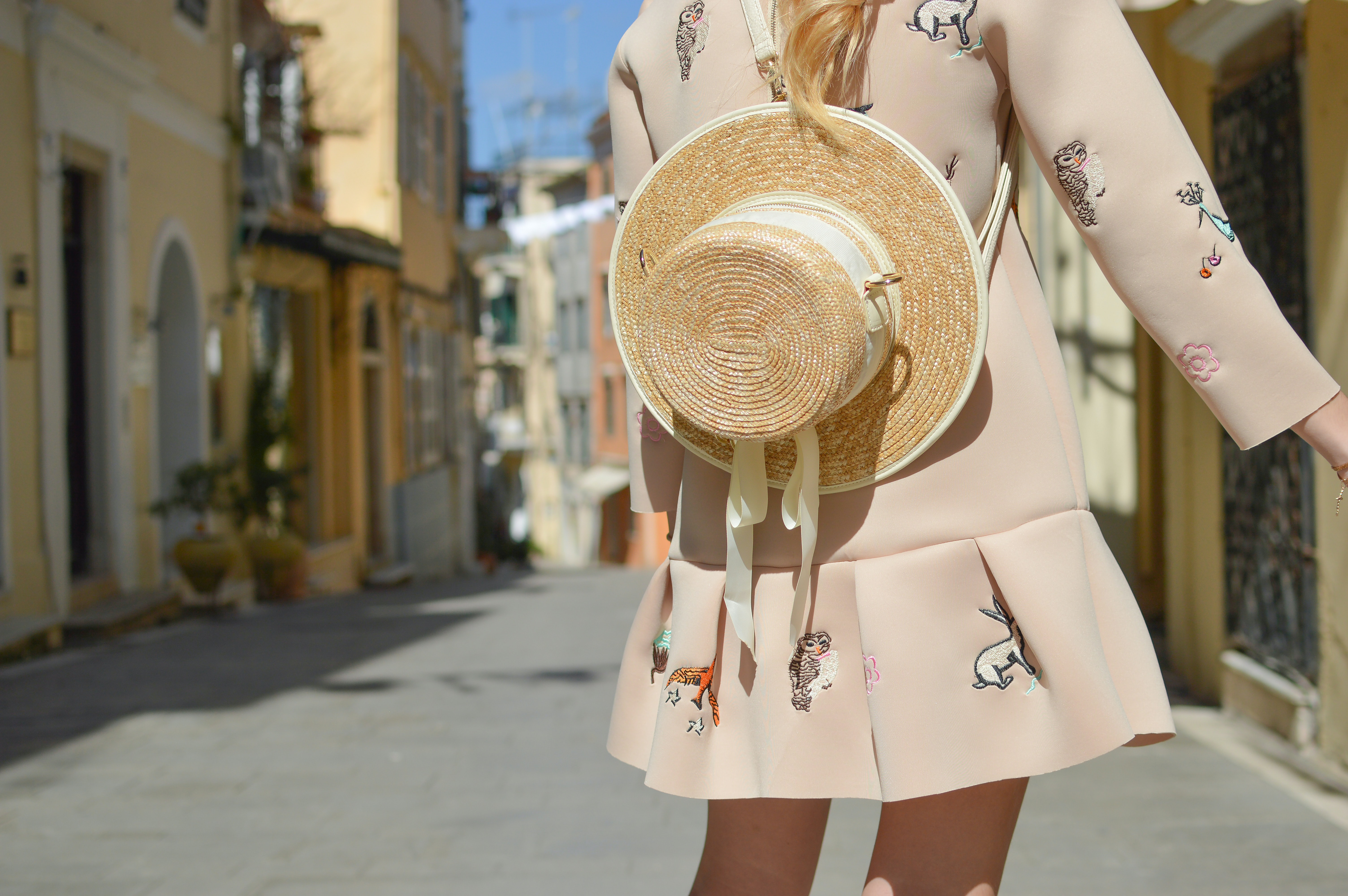 A woman in a pink dress with a straw hat hanging from her back in Corfu