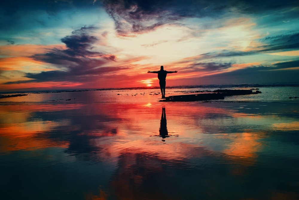 silhouette of person standing on rock surrounded by body of water