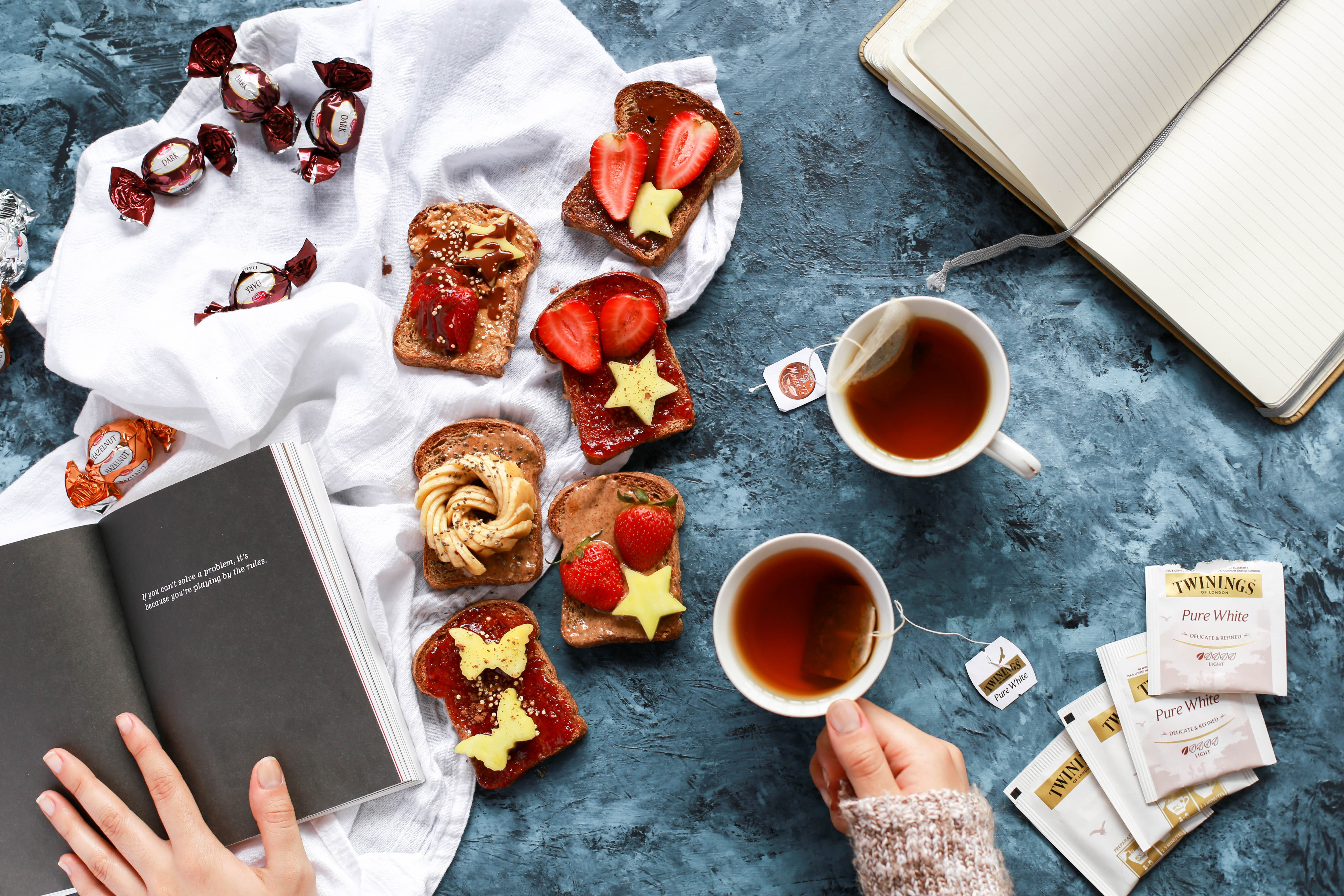 Person reading, sipping English tea and eating berries and bananas on toast with chocolates