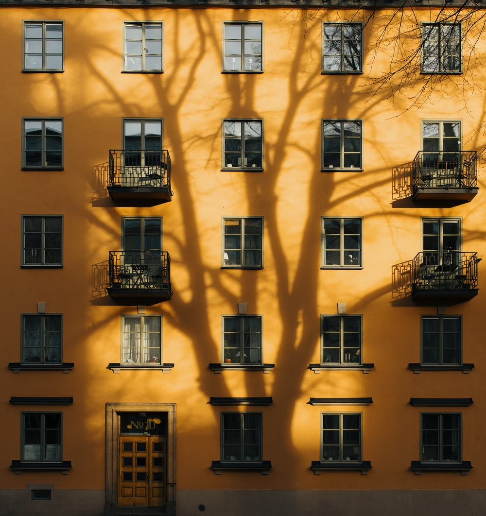 orange concrete building with tree shadow during daytime