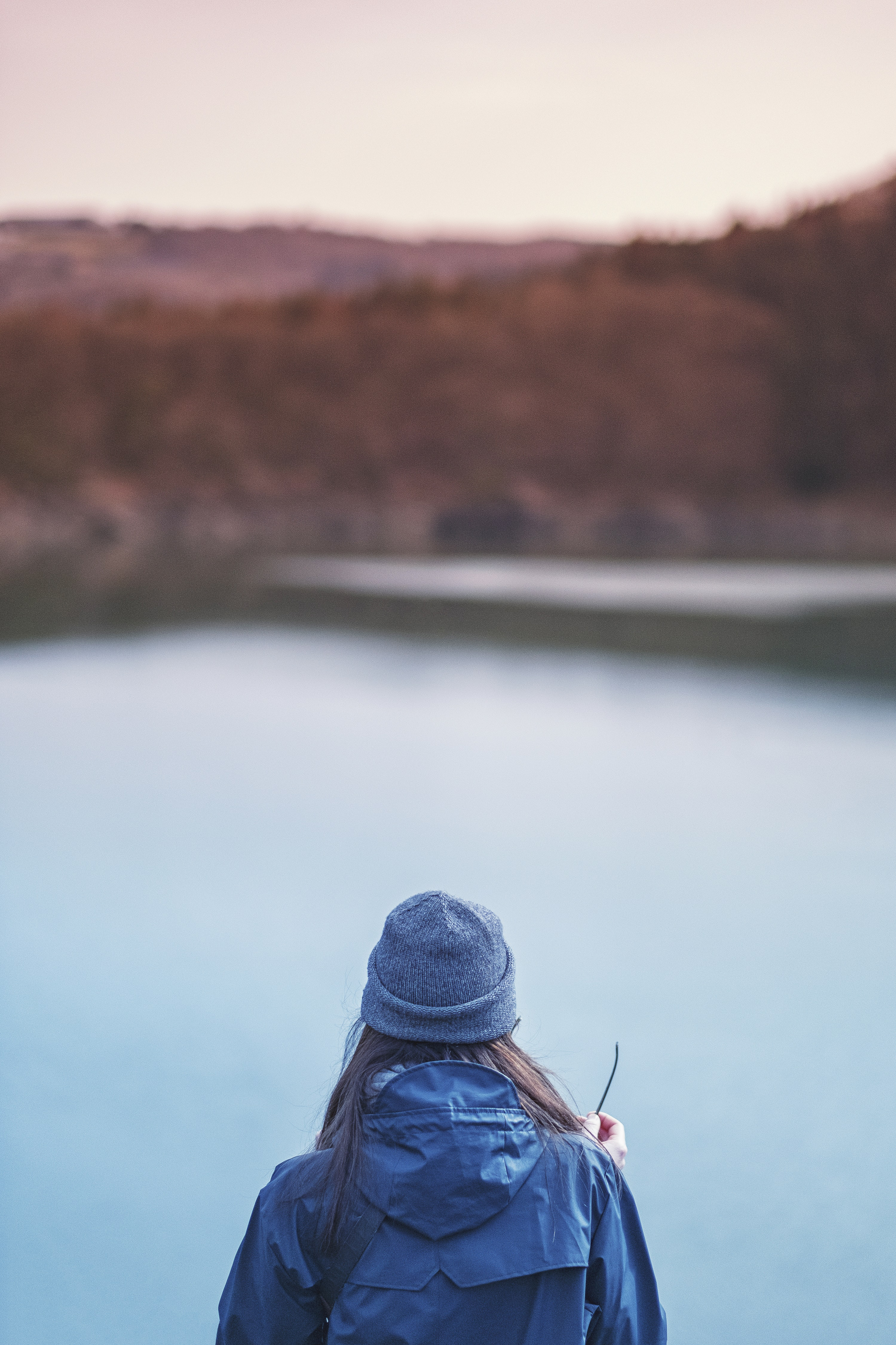 A woman staring out into a lake while wearing a blue jacket and beanie cap