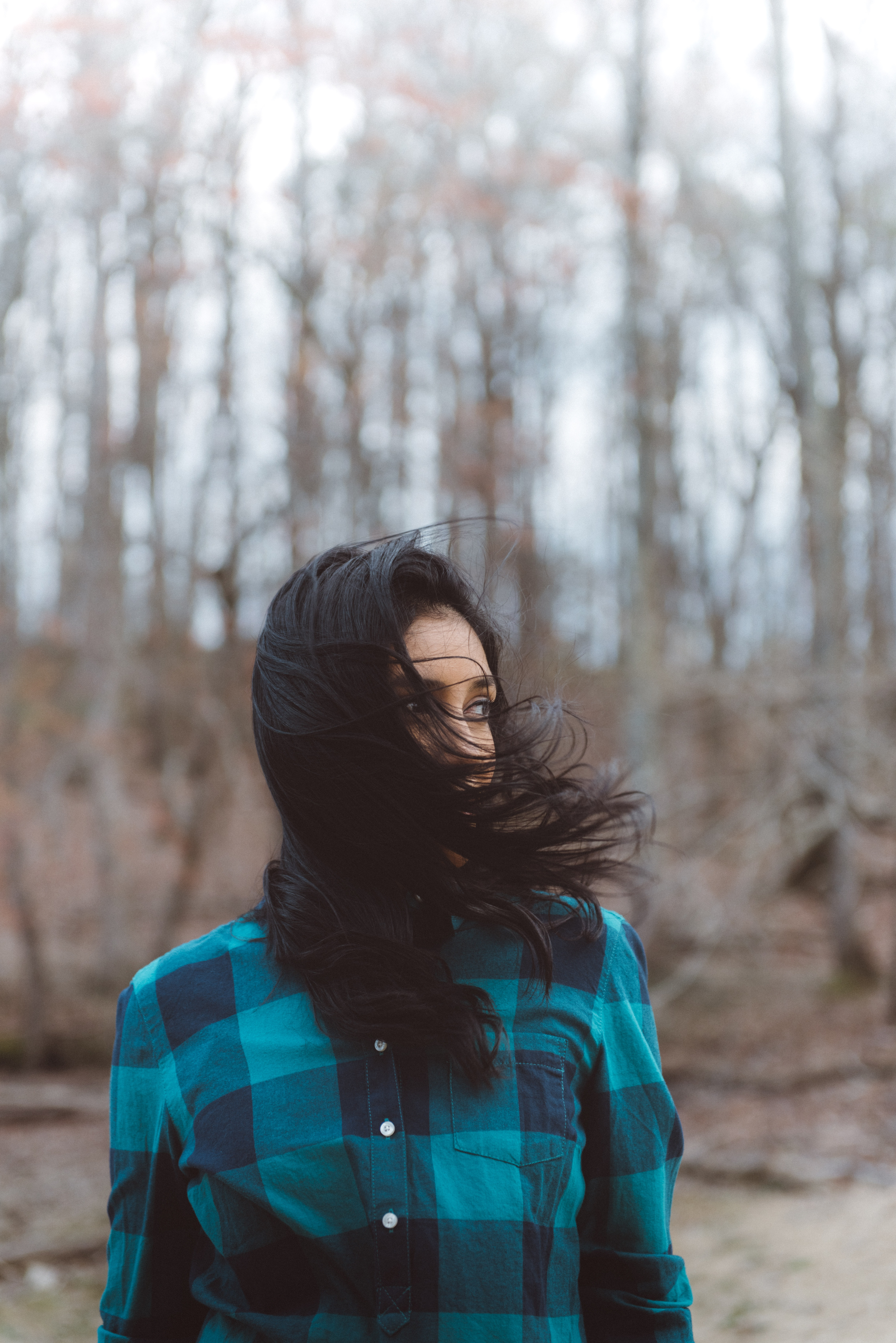Woman with black hair wearing a blue, plaid flannel shirt in the woods