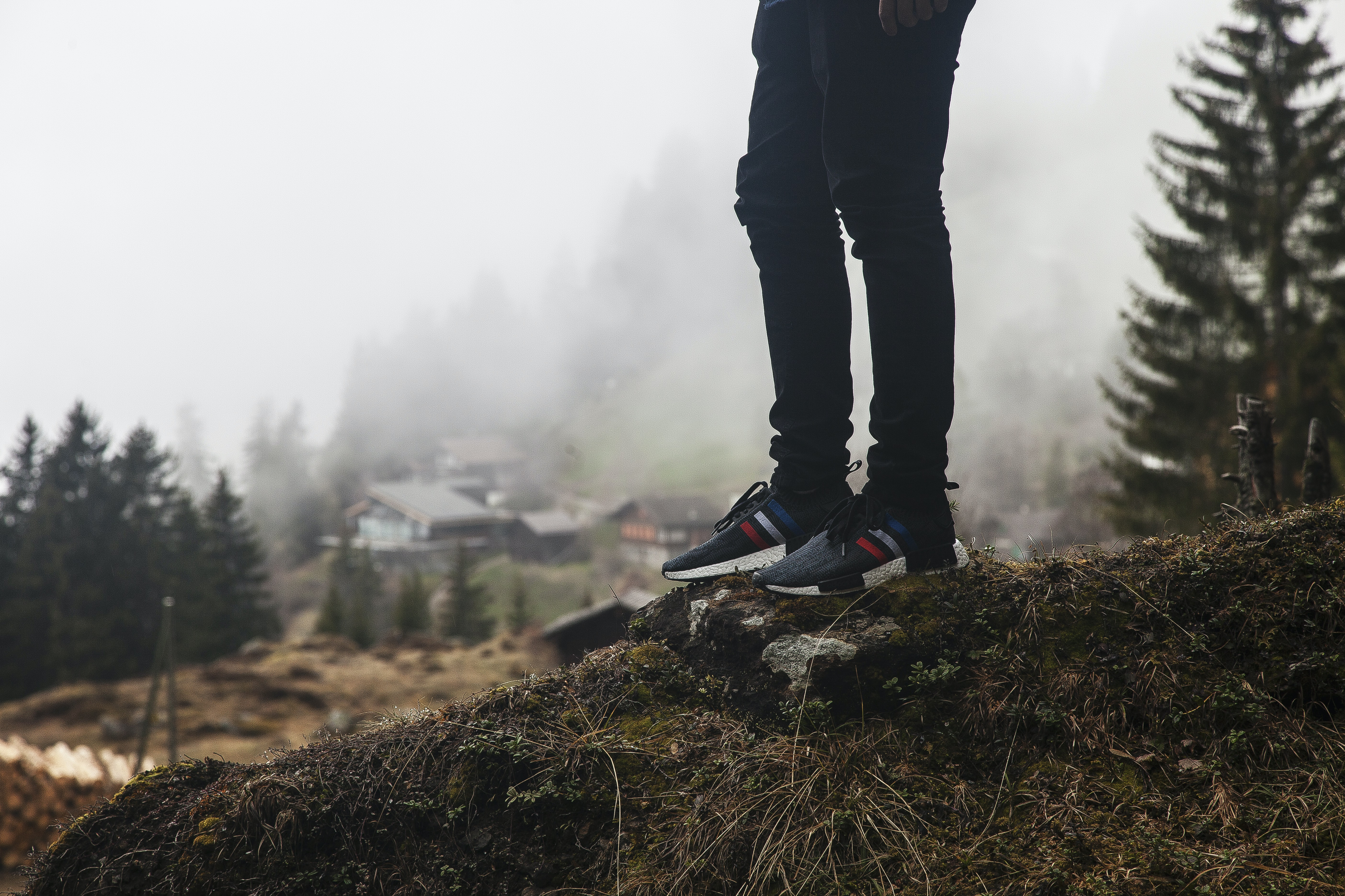 Person wearing jeans and casual sneakers atop a hill near cottages