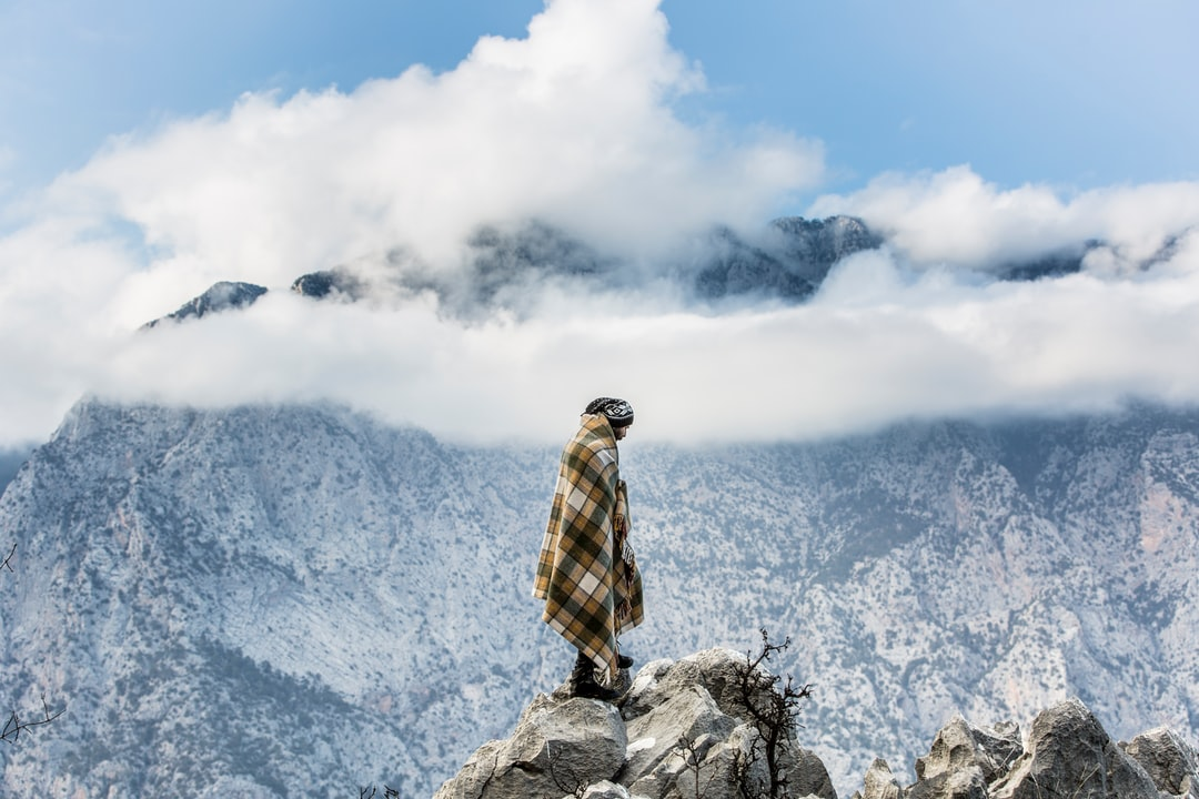 A man wrapped in a plaid blanket standing on rocks overlooking a steep mountain slope