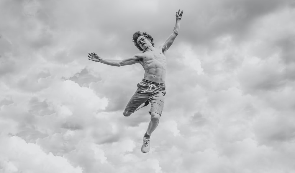 grayscale photo of person jumping overlooking clouds
