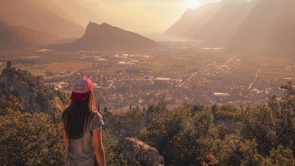 woman wearing gray shirt facing town near mountain during daytime