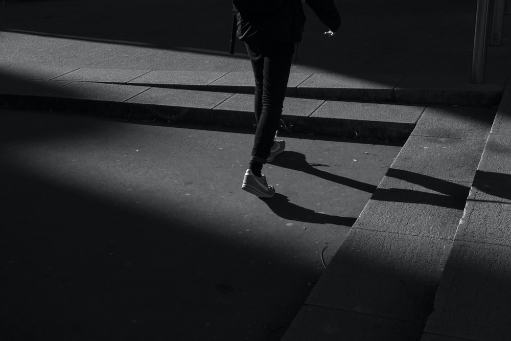 person wearing black pants and white shoes walking near gray concrete stairs