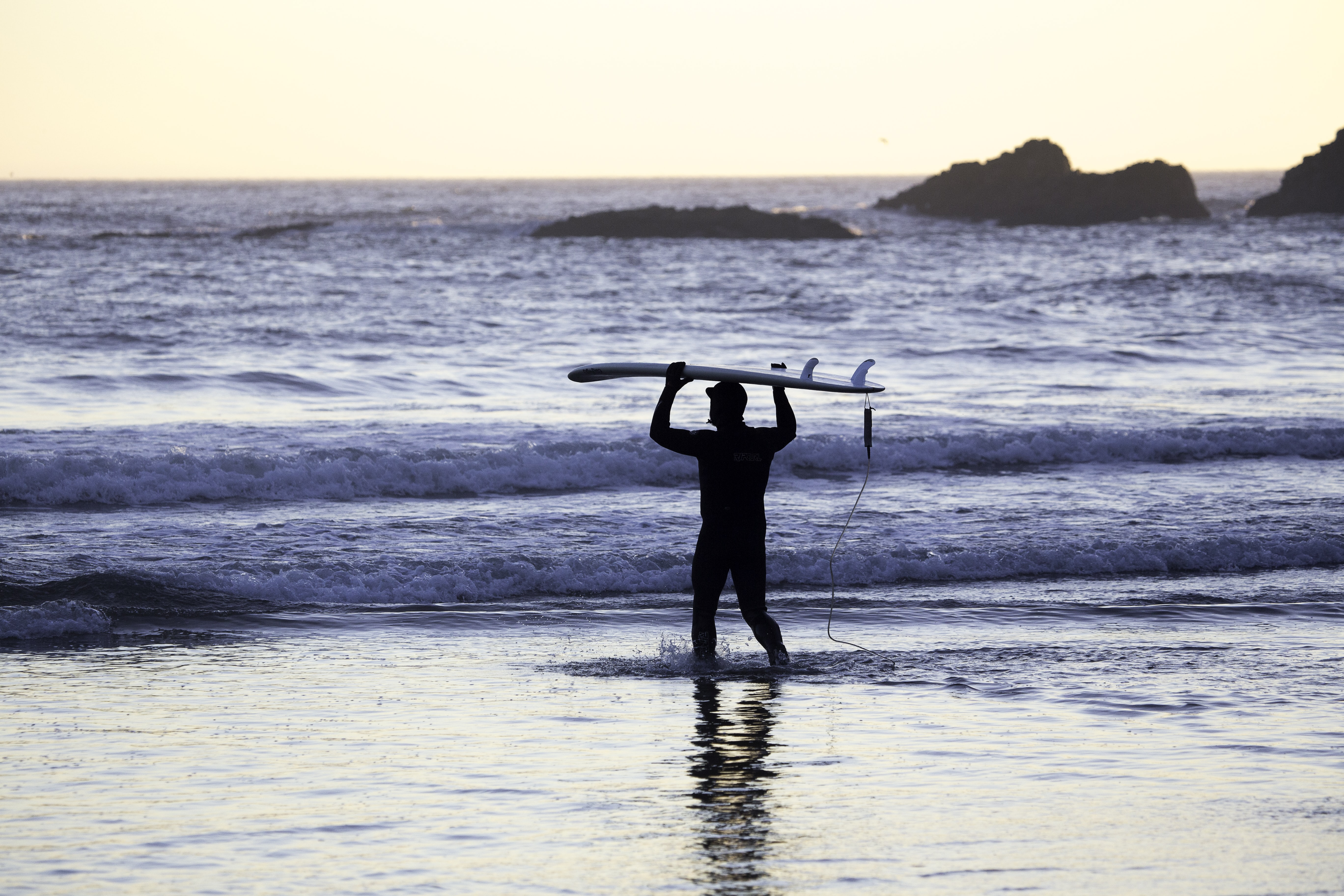 A silhouetted surfer carrying a board over his head, walking towards the sea at sunrise or sunset