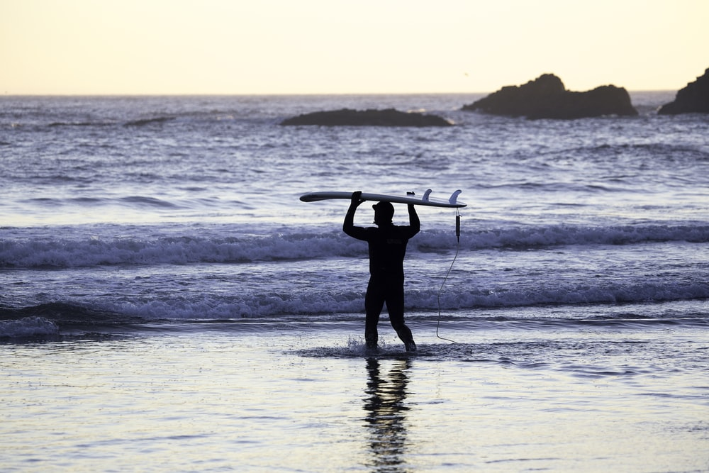 silhouette of man holding surfing board in seashore during daytime