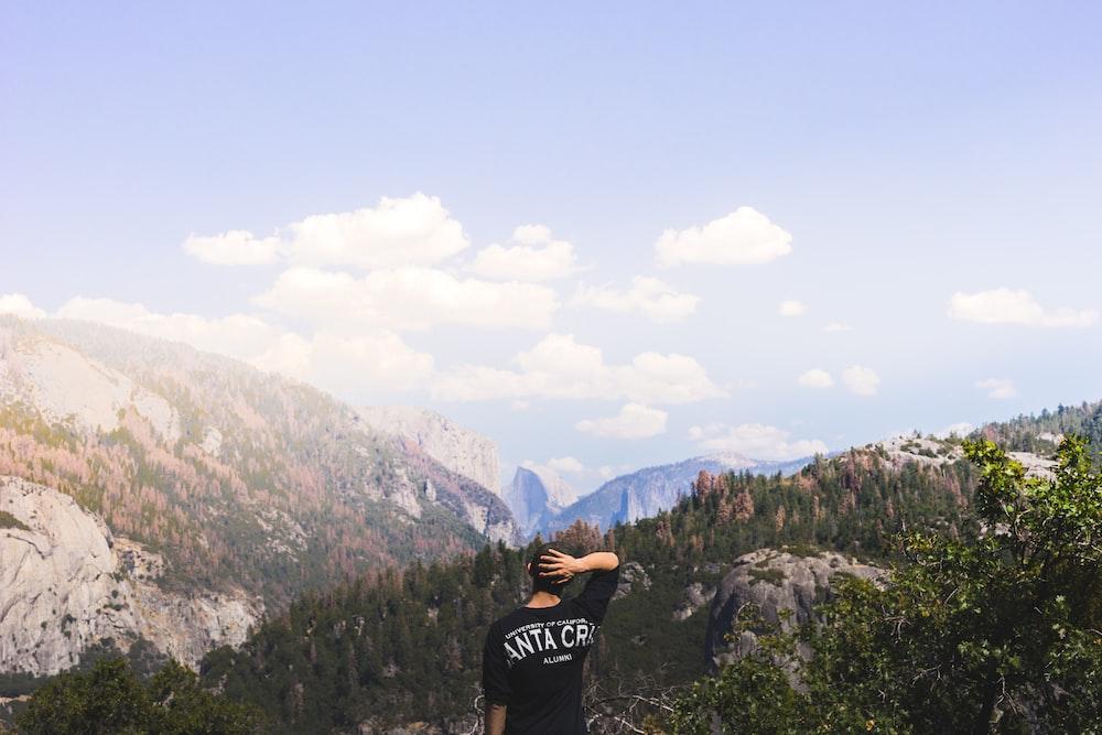 man standing near mountain under clear syk