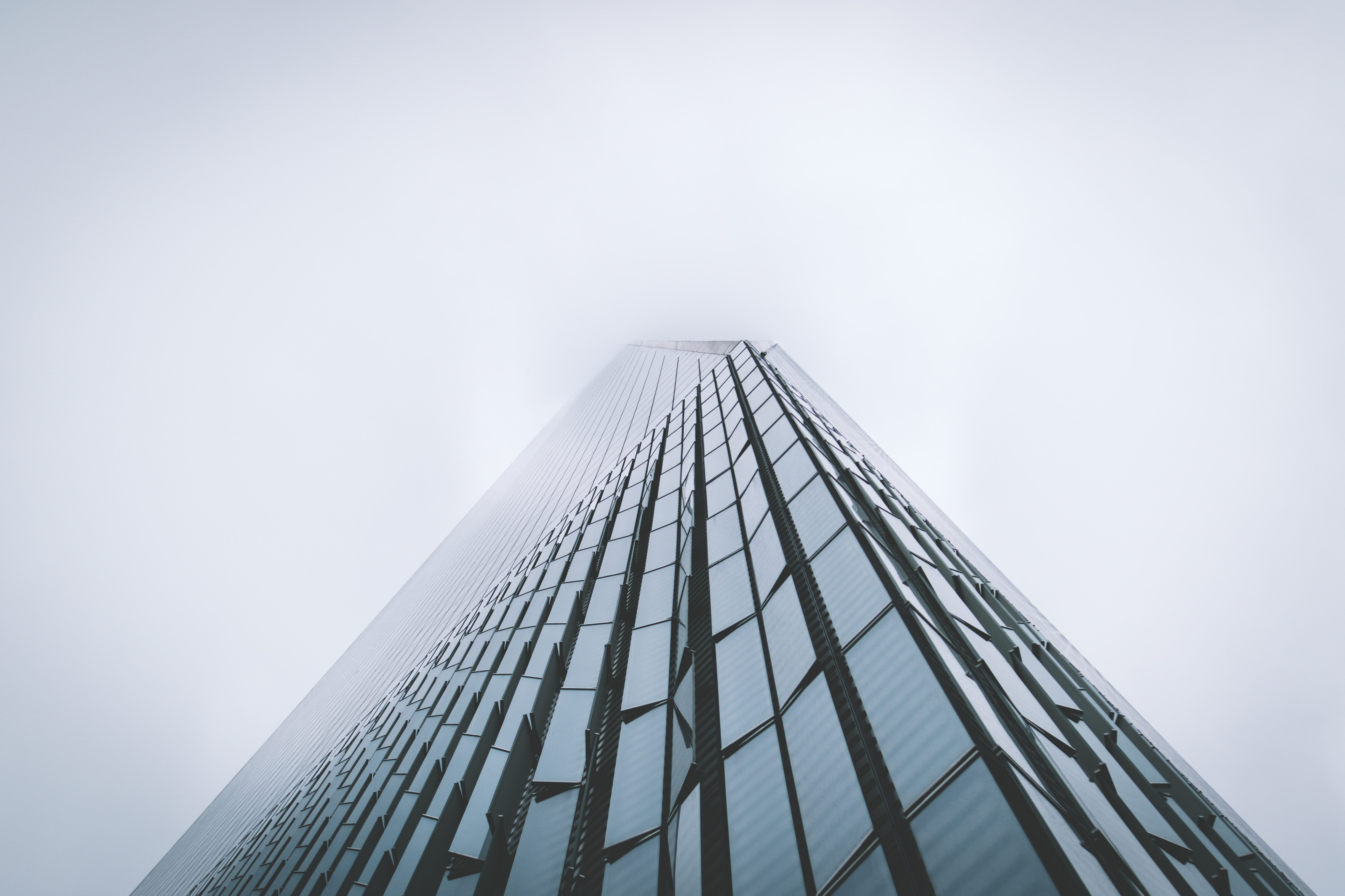 The towering facade of One World Trade Center building shrouded in fog