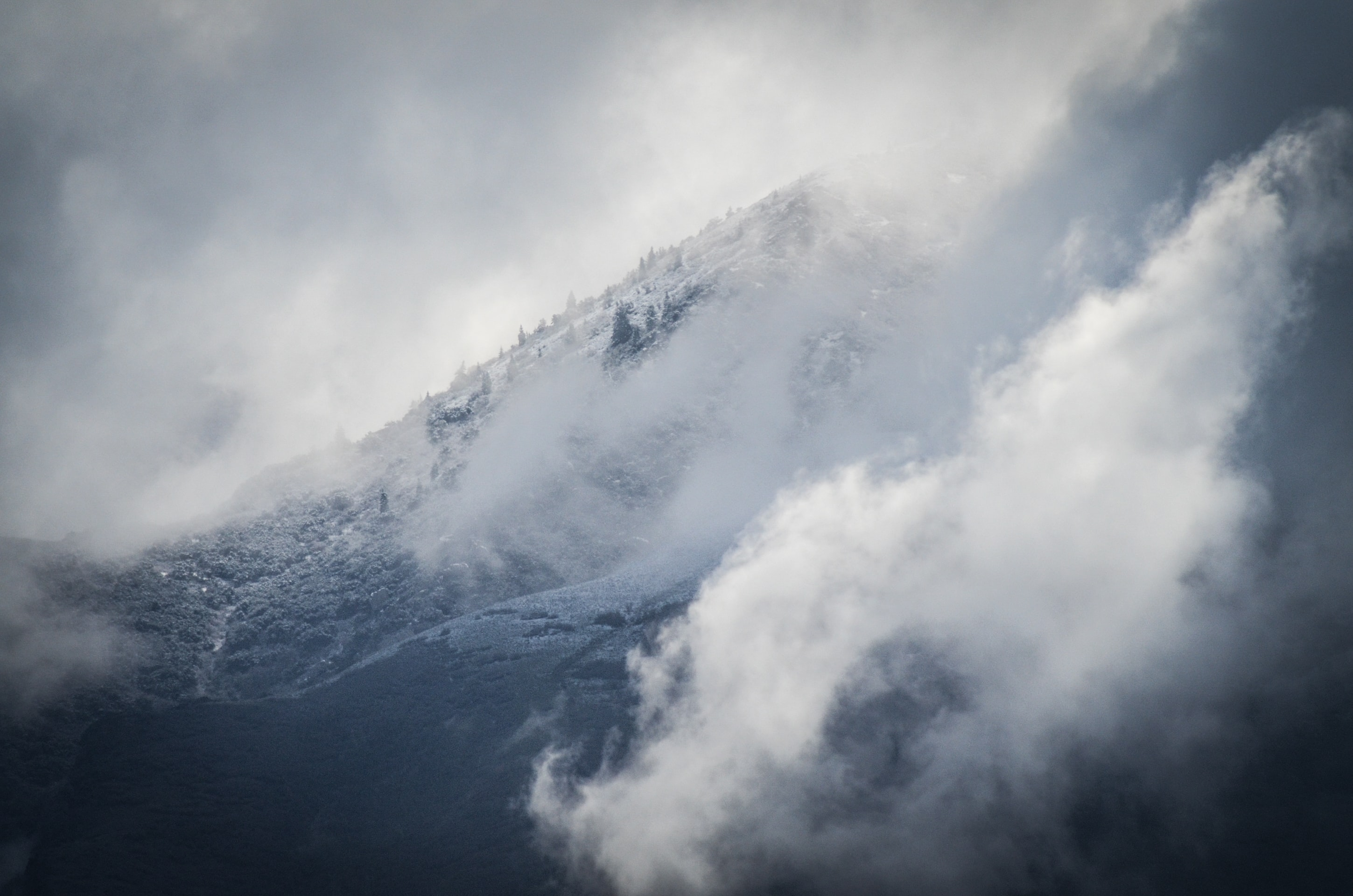 Fog rolls in over snowy mountains during winter in Lone Peak Parkway