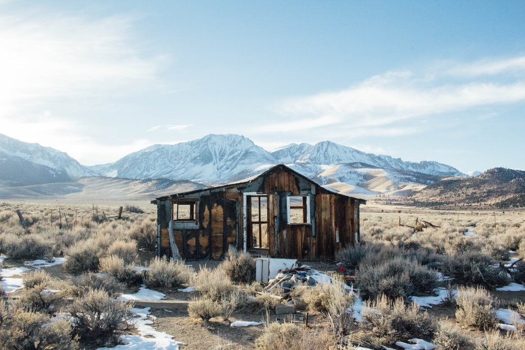 Крушение коричневый деревянный дом, стоящий на поле коричневой траве в дневное время