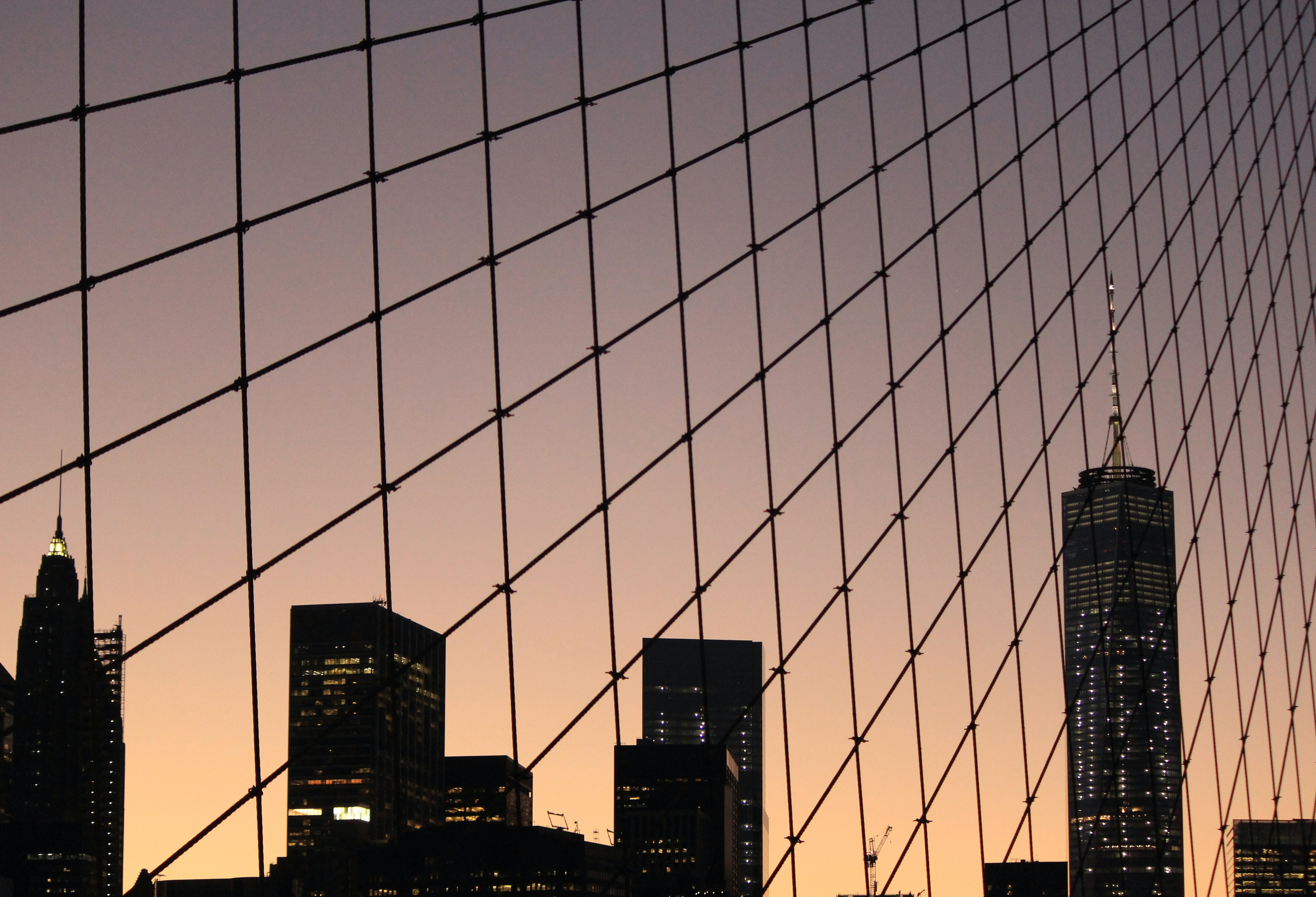 Looking up at the New York City skyline through a chain link fence at sunset