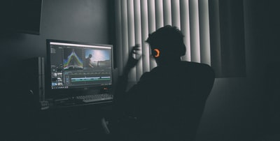 shallow focus photography of man listing to music in front of the computer