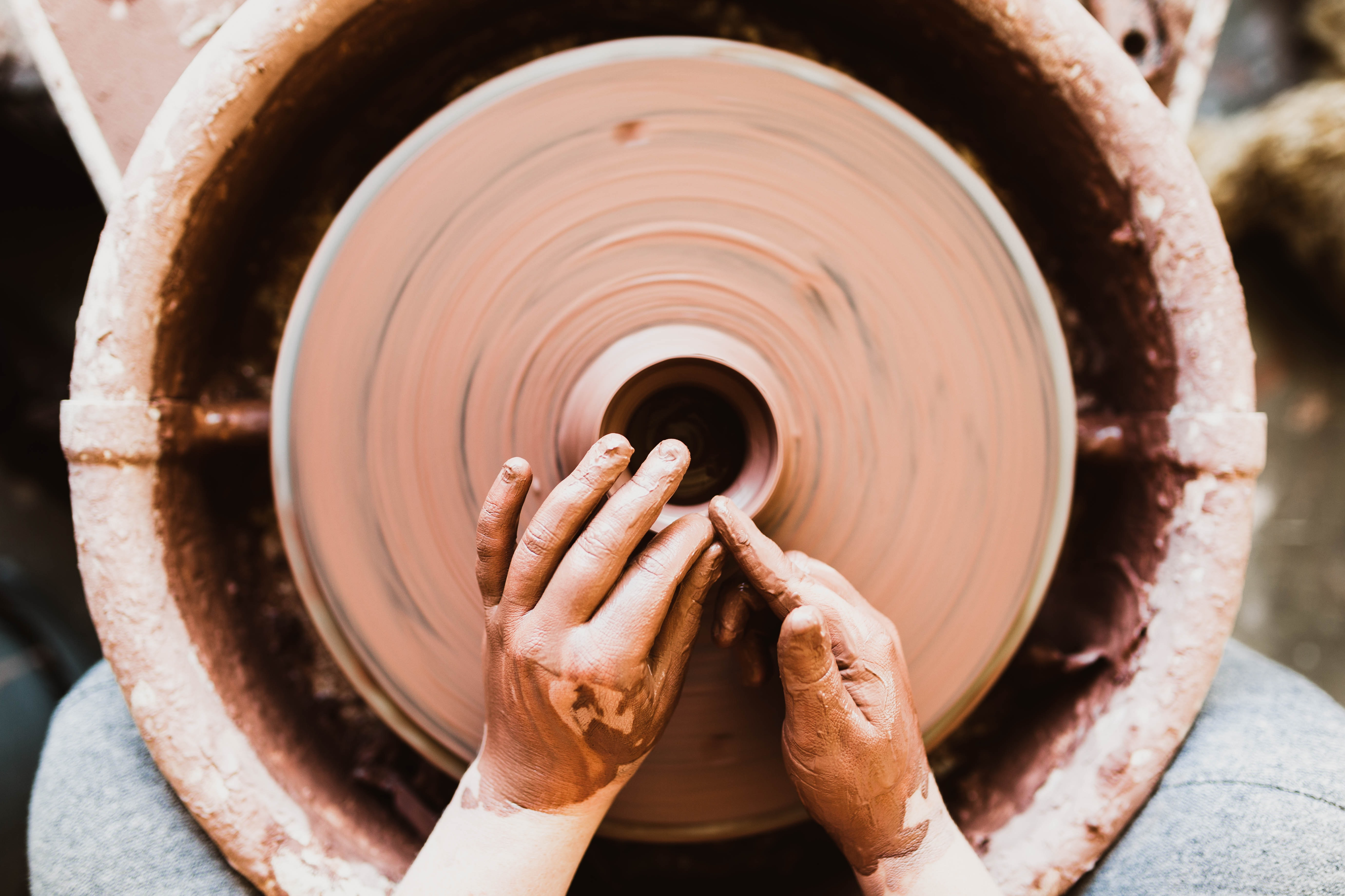 A person's hands crafting pottery on a spinning wheel