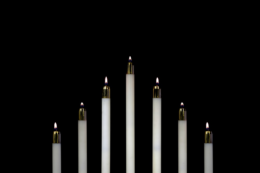 seven white candles closeup photography