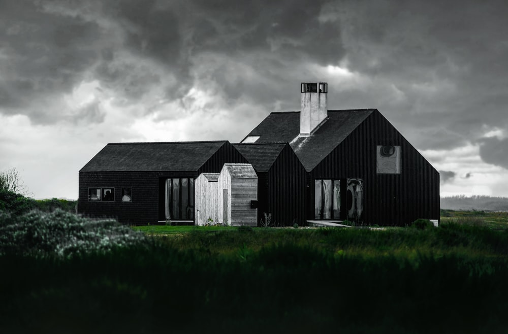 black and white house beside green grass field